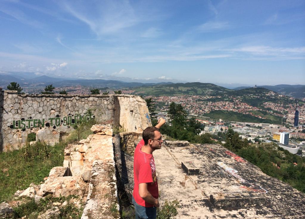 Skender i en ruin på Trebević-berget ovanför Sarajevo, en plats där serbiska krypskyttar hade bra utsikt över stan. Han pekar ut området som en gång i tiden var Ingemansland.