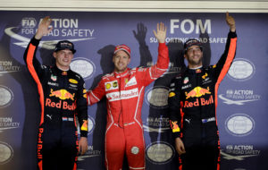 Formula One F1 - Singapore Grand Prix 2017 - Singapore - September 16, 2017 Ferrari's Sebastian Vettel celebrates pole position in qualifying with Red Bull's Max Verstappen and Daniel Ricciardo REUTERS/Jeremy Lee