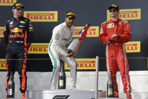 Mercedes driver Lewis Hamilton of Britain celebrates on the podium after winning the French Formula One Grand Prix at the Paul Ricard racetrack, in Le Castellet, southern France, Sunday, June 24, 2018. Second placed Red Bull driver Max Verstappen of the Netherlands, left and third placed Ferrari driver Kimi Raikkonen of Finland, stand on the podium with Hamilton.(AP Photo/Claude Paris)