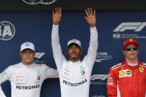 Mercedes' British driver Lewis Hamilton (C), who took the dominant pole position, celebrates with his teammate Mercedes' Finnish driver Valtteri Bottas, next to Ferrari's Finnish driver Kimi Raikkonen (R) on the podium after the qualifying session on the eve of the Formula One Hungarian Grand Prix at the Hungaroring circuit in Mogyorod near Budapest, Hungary, on July 28, 2018. Lewis Hamilton finished ahead of Mercedes' Finnish driver Valtteri Bottas and Ferrari's Finnish driver Kimi Raikkonen. / AFP PHOTO / ATTILA KISBENEDEK