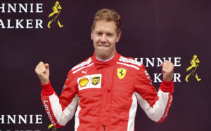 Ferrari driver Sebastian Vettel of Germany jubilates on the podium after winning the Belgian Formula One Grand Prix in Spa-Francorchamps, Belgium, Sunday, Aug. 26, 2018. Mercedes driver Lewis Hamilton of Britain placed second and Red Bull driver Max Verstappen of the Netherlands placed third. (AP Photo/Geert Vanden Wijngaert)
