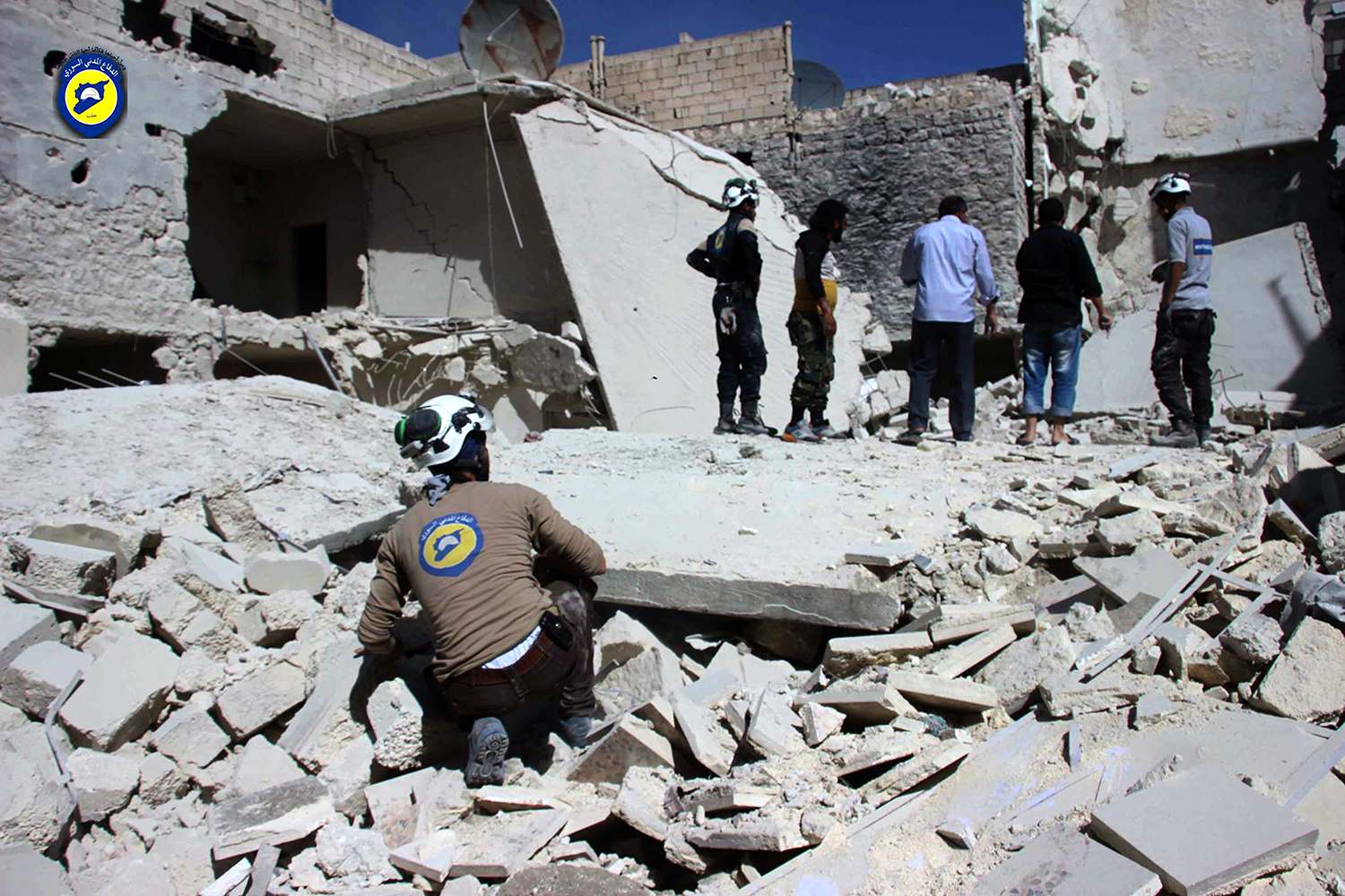 """This photo provided by the Syrian Civil Defense group known as the White Helmets, shows members of Civil Defense inspecting damaged buildings after airstrikes hit the Bustan al-Qasr neighborhood of Aleppo, Syria, Sunday, Sept. 25, 2016. A broad coalition of Syrian rebels denounced international negotiations for peace as """"meaningless"""" on Sunday, as the U.N. Security Council prepared to convene an emergency meeting about the spiraling violence in Syria. (Syrian Civil Defense White Helmets via AP)"""