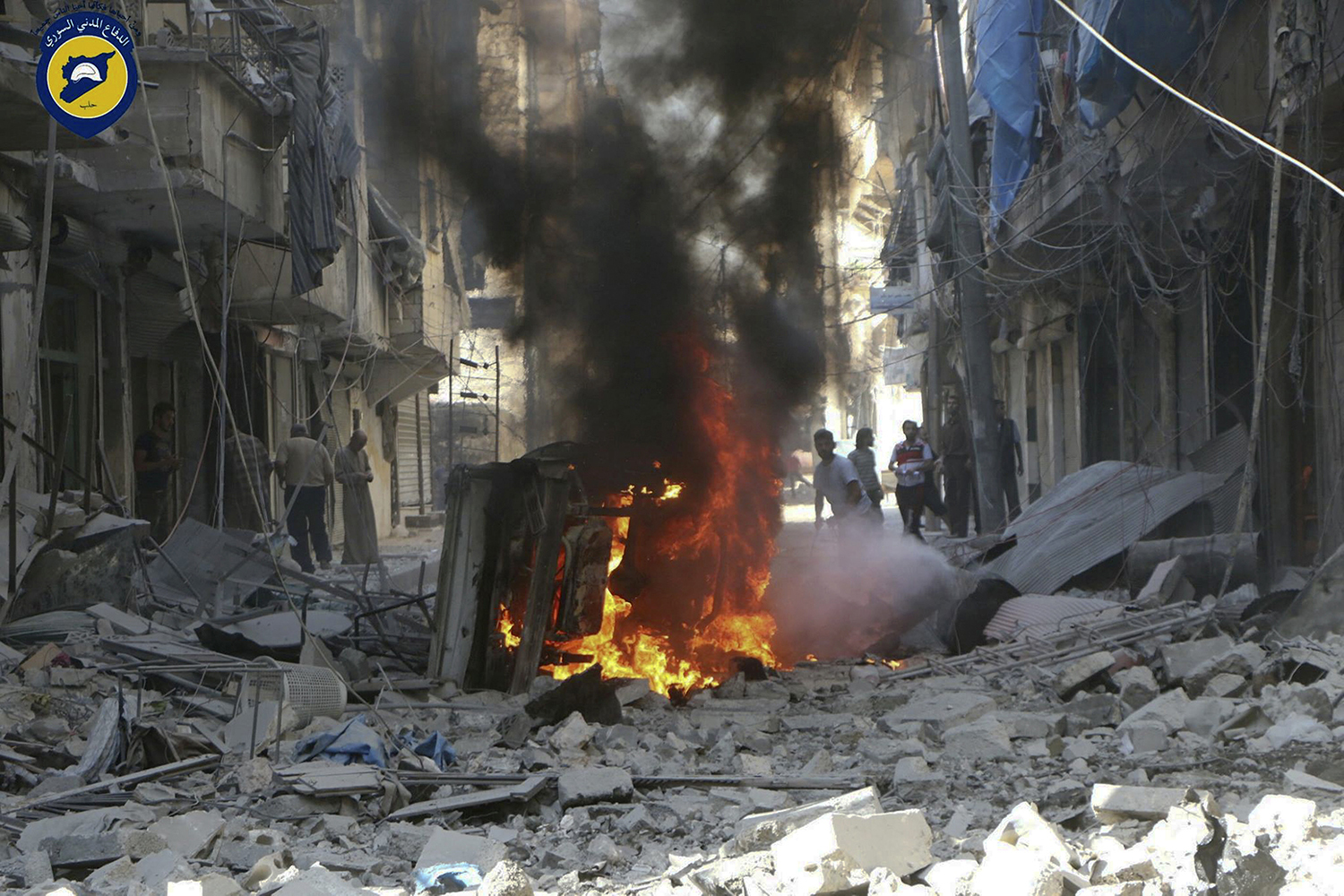 In this photo provided by the Syrian Civil Defense group known as the White Helmets, Syrians inspect damaged buildings after airstrikes by government helicopters on the rebel-held Aleppo neighborhood of Mashhad, Syria, Tuesday Sept. 27, 2016. With diplomacy in tatters and a month left to go before U.S. elections, the Syrian government and its Russian allies are using the time to try and recapture the northern city of Aleppo, mobilizing pro-government militias in the Old City and pressing ahead with the most destructive aerial campaign of the past five years. (Syrian Civil Defense White Helmets via AP)