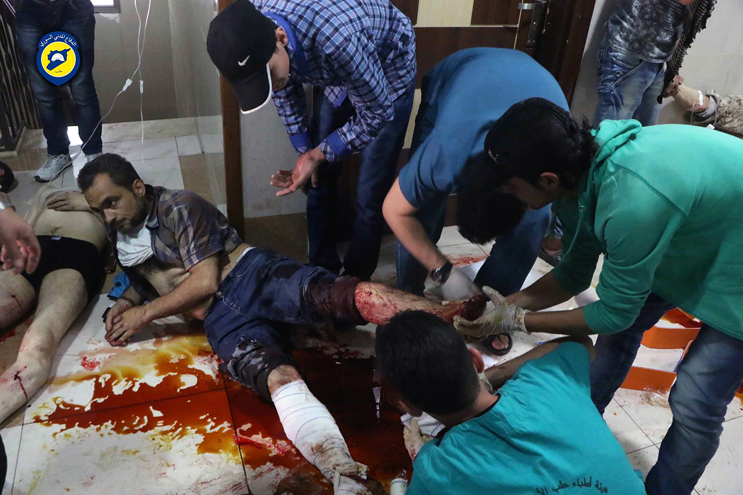 """This photo provided by the Syrian Civil Defense group known as the White Helmets, shows victims of airstrikes receiving treatment on the floor of a clinic, in Aleppo, Syria, Sunday, Sept. 25, 2016. A broad coalition of Syrian rebels denounced international negotiations for peace as """"meaningless"""" on Sunday, as the U.N. Security Council prepared to convene an emergency meeting about the spiraling violence in Syria. (Syrian Civil Defense White Helmets via AP)"""