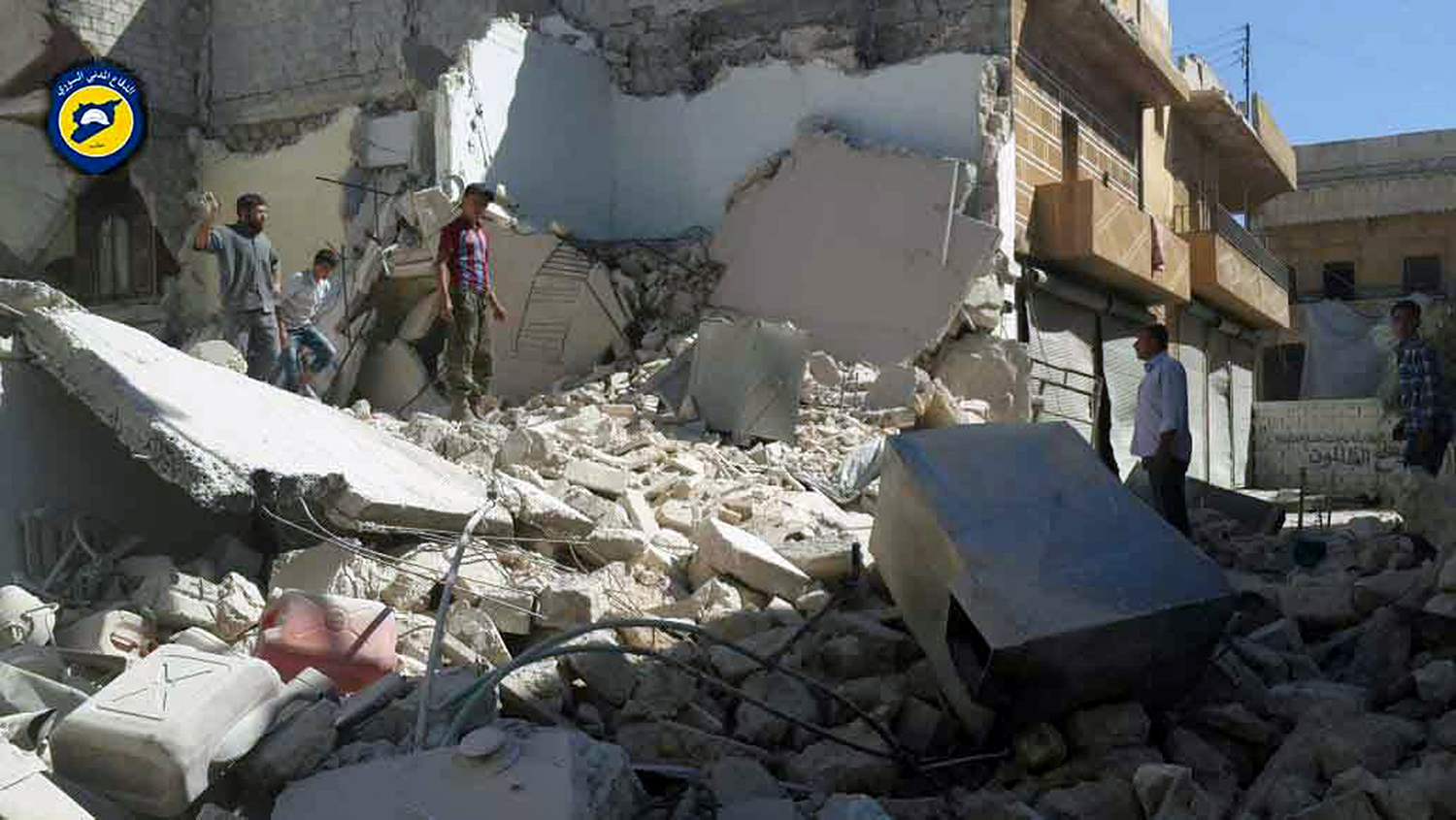 """This photo provided by the Syrian Civil Defense group known as the White Helmets, shows Syrians inspecting damaged buildings after airstrikes hit the Bustan al-Qasr neighborhood of Aleppo, Syria, Sunday, Sept. 25, 2016. A broad coalition of Syrian rebels denounced international negotiations for peace as """"meaningless"""" on Sunday, as the U.N. Security Council prepared to convene an emergency meeting about the spiraling violence in Syria. (Syrian Civil Defense White Helmets via AP)"""