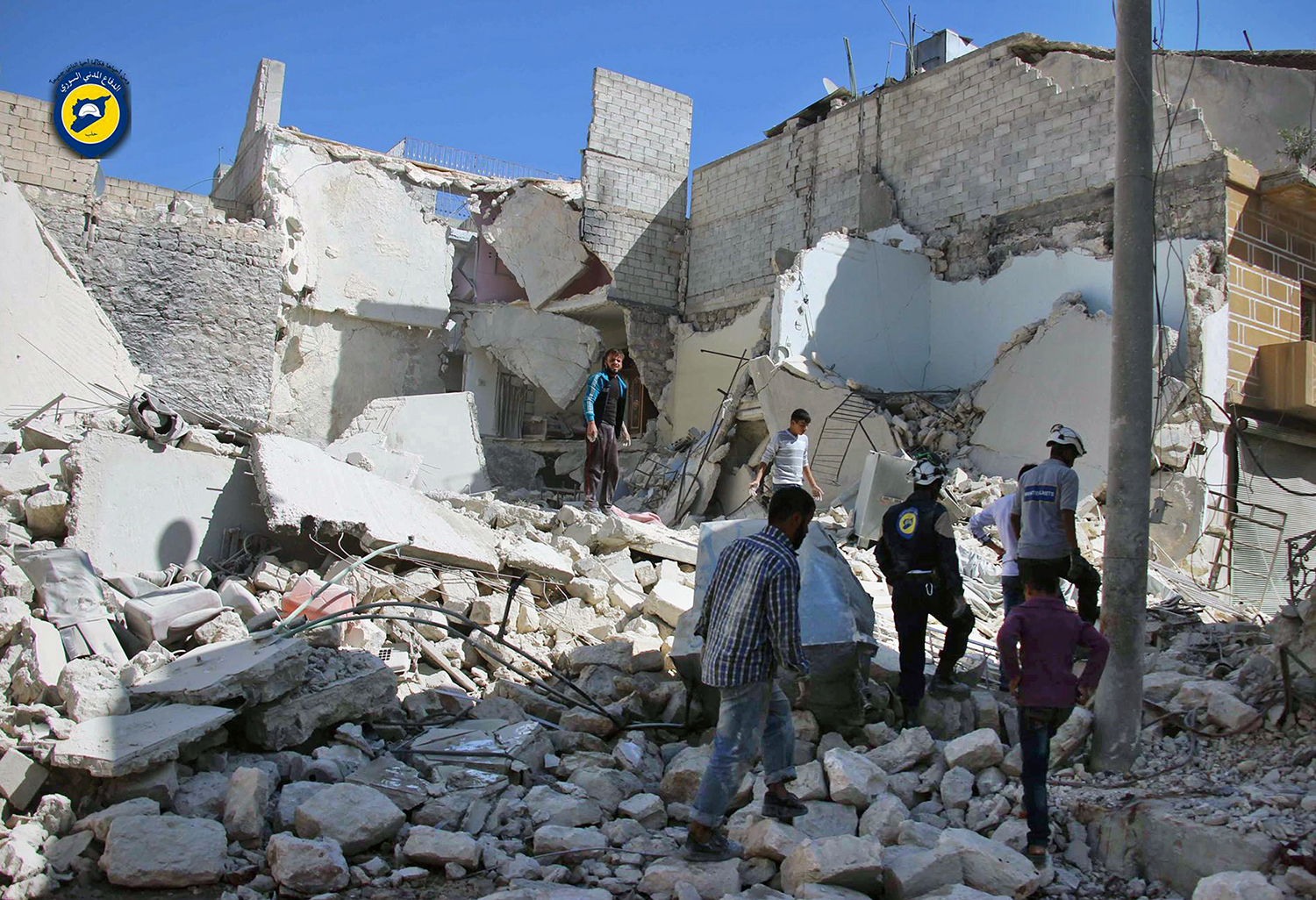 """In this photo provided by the Syrian Civil Defense group known as the White Helmets, members of the Civil Defense group and residents inspect damaged buildings after airstrikes hit the Bustan al-Qasr neighborhood in Aleppo, Syria, Sunday, Sept. 25, 2016. A broad coalition of Syrian rebels denounced international negotiations for peace as """"meaningless"""" on Sunday, as the U.N. Security Council prepared to convene an emergency meeting about the spiraling violence in Syria. (Syrian Civil Defense White Helmets via AP)"""