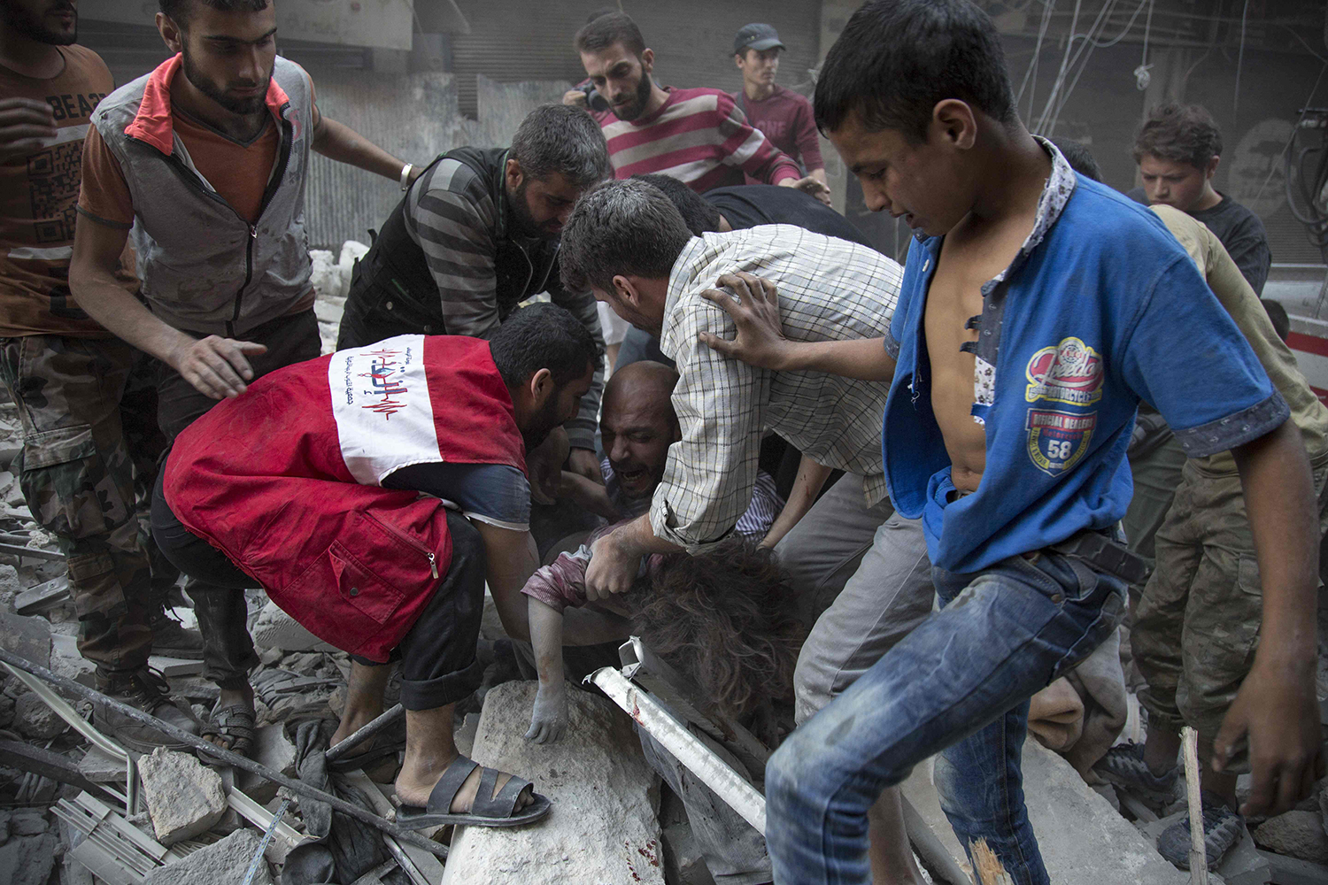 TOPSHOT - EDITORS NOTE: Graphic content / Syrians surround a man as he cries over the body of his child after she was pulled out from the rubble of a budling following government forces air strikes in the rebel held neighbourhood of Al-Shaar in Aleppo on September 27, 2016. Syria's army took control of a rebel-held district in central Aleppo, after days of heavy air strikes that have killed dozens and sparked allegations of war crimes. / AFP PHOTO / KARAM AL-MASRI / TT / kod 444