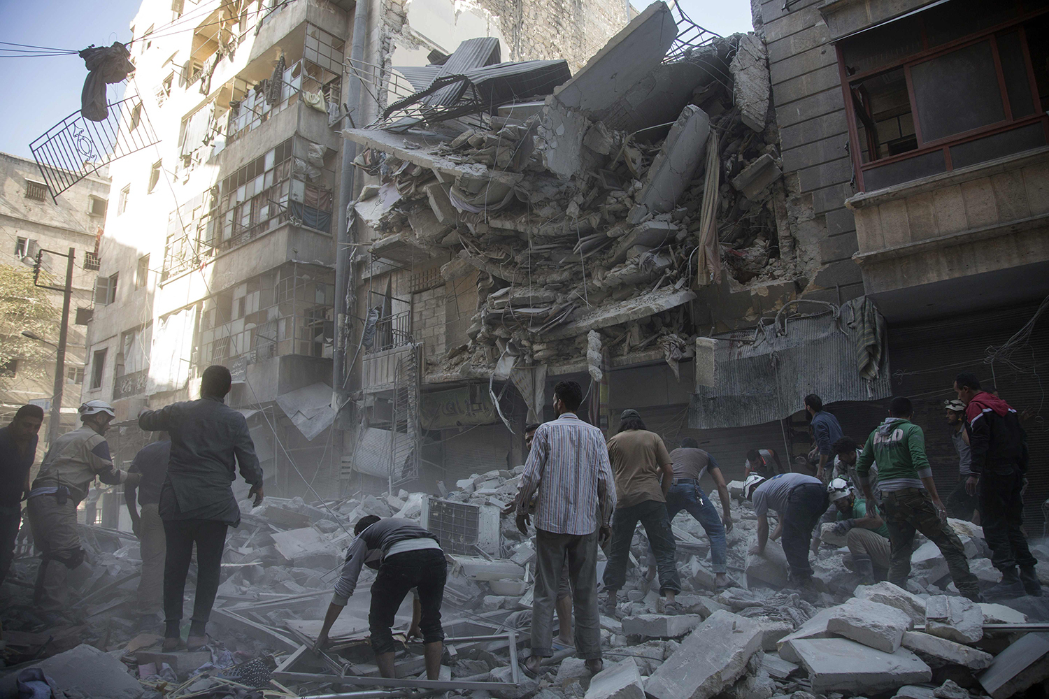 TOPSHOT - Syrian civilians and rescuers gather at site of government forces air strikes in the rebel held neighbourhood of Al-Shaar in Aleppo on September 27, 2016. Syria's army took control of a rebel-held district in central Aleppo, after days of heavy air strikes that have killed dozens and sparked allegations of war crimes. / AFP PHOTO / KARAM AL-MASRI / TT / kod 444