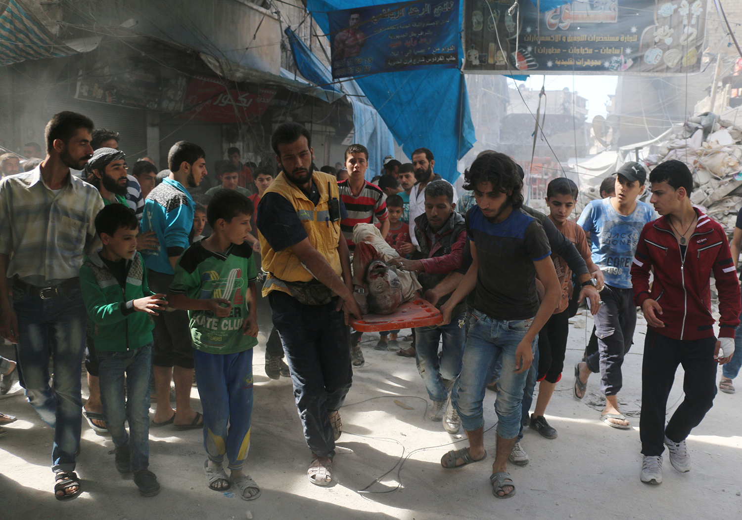TOPSHOT - Syrians carry the body of a man following air strikes on the rebel-held Fardous neighbourhood of the northern embattled Syrian city of Aleppo on October 12, 2016.  / AFP PHOTO / AMEER ALHALBI / TT / kod 444