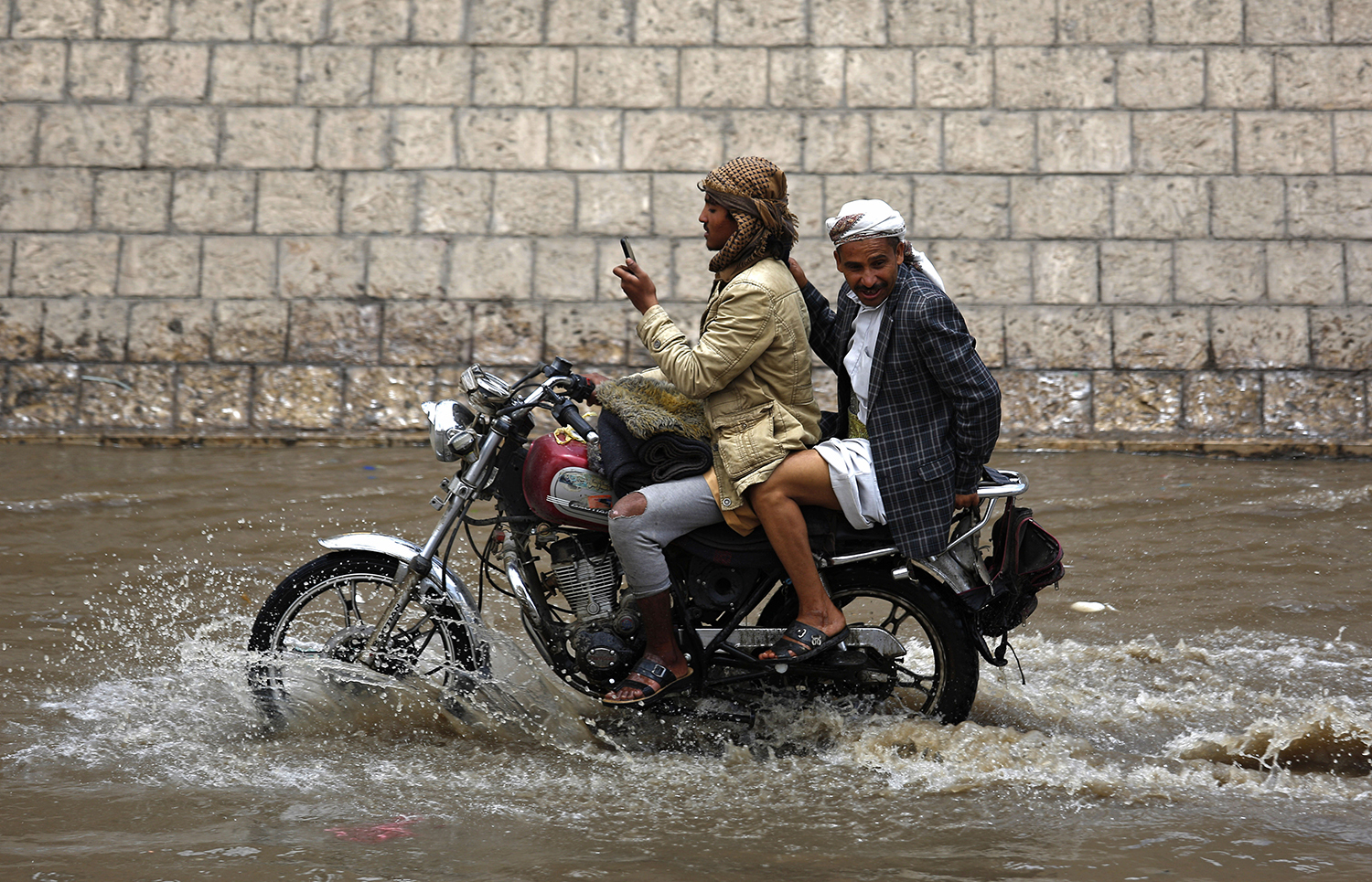 A man looks at his mobile phone while riding a motorcycle in floodwaters on a rainy day in Sanaa, Yemen, Wednesday, April 13, 2016. (AP Photo/Hani Mohammed)