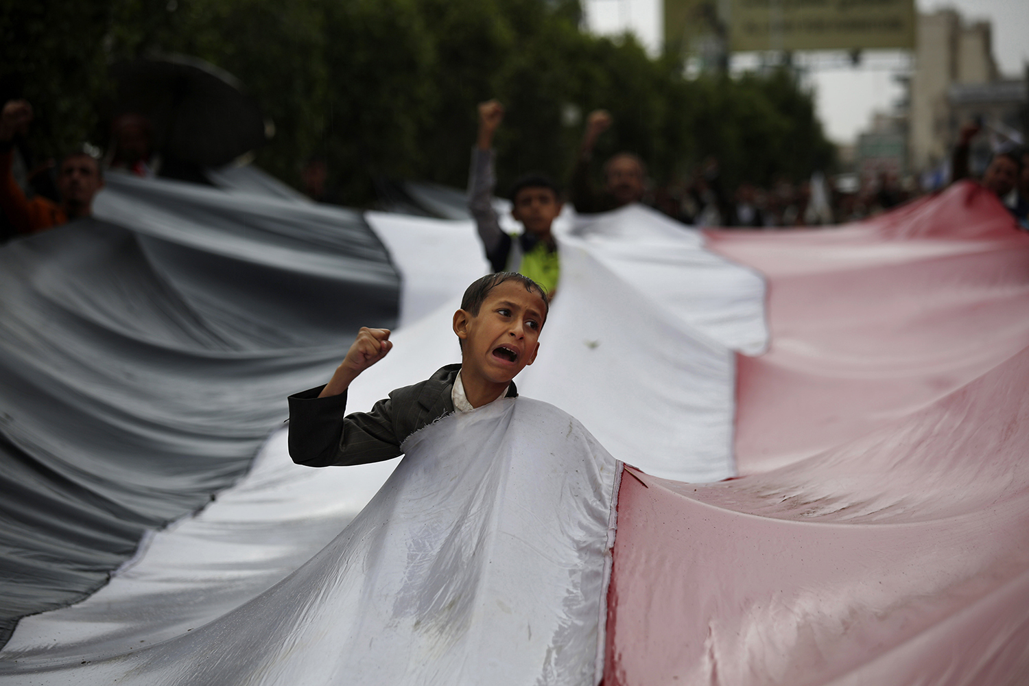 A boy chants slogans through a gap in a national flag raised by Shiite rebels, known as Houthis, during a protest against Saudi-led airstrikes in Sanaa, Yemen, Friday, April 15, 2016. (AP Photo/Hani Mohammed)