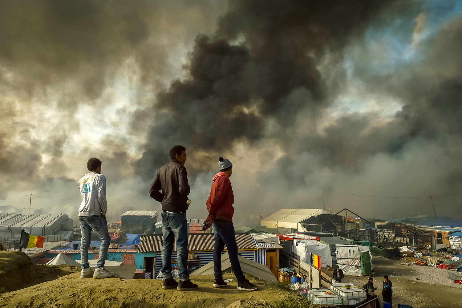 """TOPSHOT - Migrants stand on a hill overlooking the """"Jungle"""" migrant camp in Calais, northern France, as smoke rises on October 26, 2016 during a massive operation to clear the squalid settlement where 6,000-8,000 people have been living in dire conditions. Fresh fires broke out on October 26 in the """"Jungle"""" migrant camp on the second day of operations to dismantle the squalid settlement in northern France. Smoke billowed over the sprawling camp near Calais for a second day amid fears that abandoned gas cylinders could explode. / AFP PHOTO / PHILIPPE HUGUEN / TT / kod 444"""