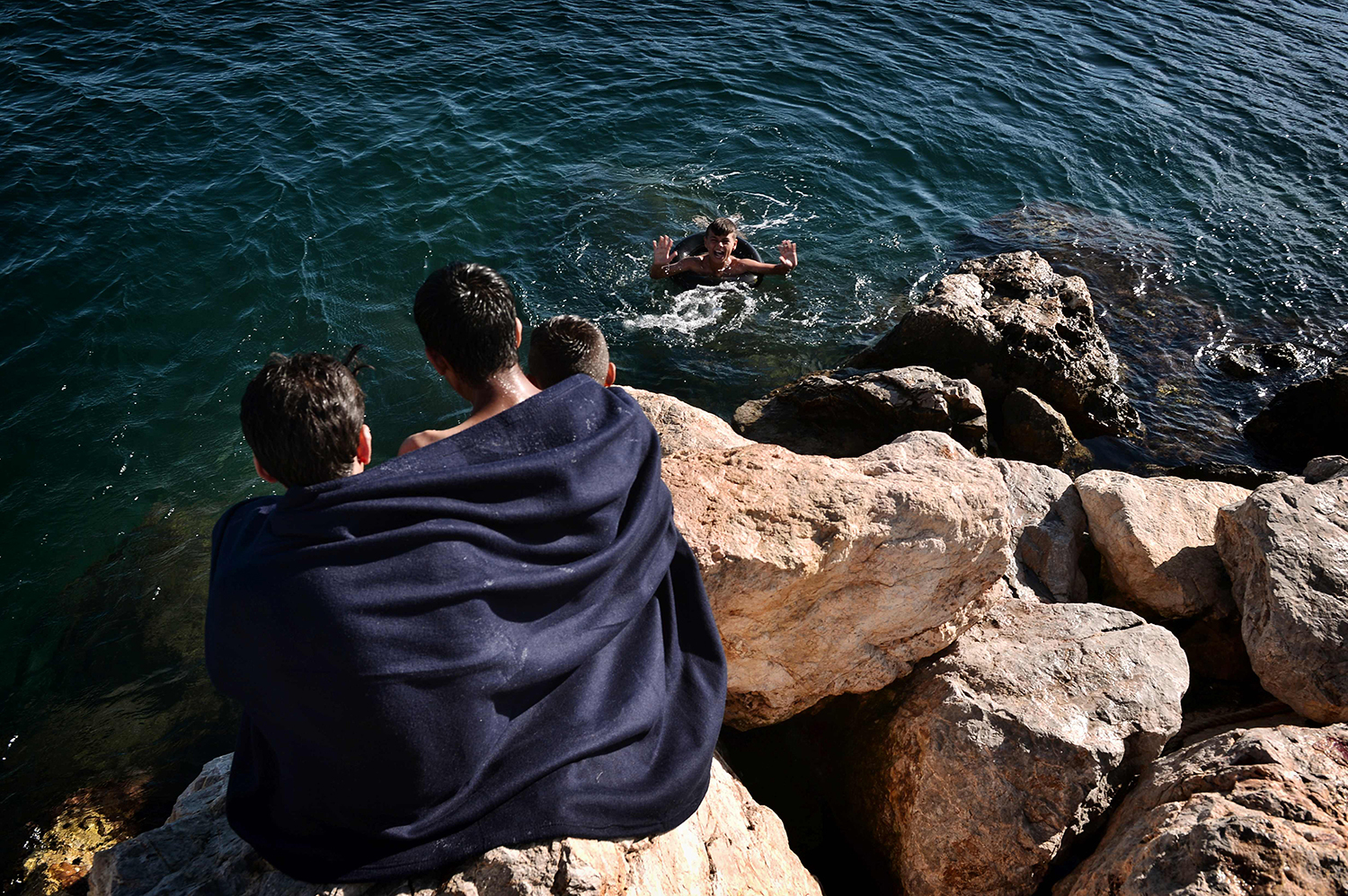 TOPSHOT - Refugee families swim in the sea by the Souda municipality-run refugee camp on the island of Chios on October 13, 2016. Greece is accommodating over 60,000 refugees and migrants stuck in the country after a succession of Balkan and EU states shut their borders earlier this year. / AFP PHOTO / LOUISA GOULIAMAKI / TT / kod 444