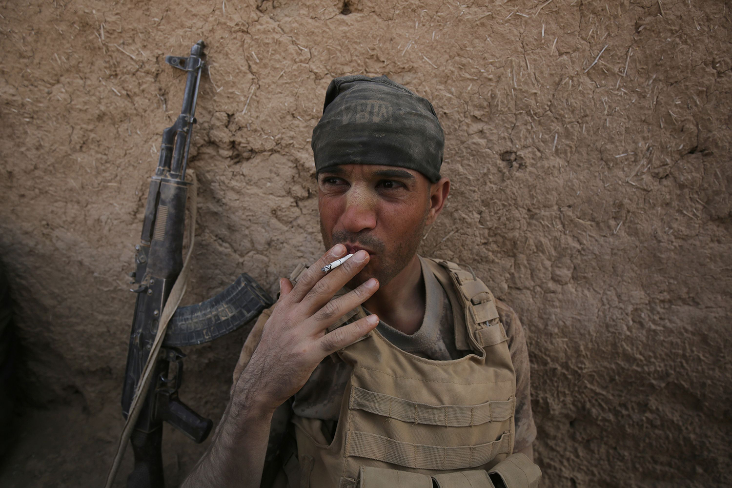 TOPSHOT - A member of the Iraqi government forces smokes a cigarette as they rest in the village of al-Khuwayn, south of Mosul, after recapturing it from Islamic State (IS) group jihadists on October 23, 2016, in part of an ongoing operation to tighten the noose around Mosul and reclaim the last major Iraqi city under IS control. / AFP PHOTO / AHMAD AL-RUBAYE / TT / kod 444