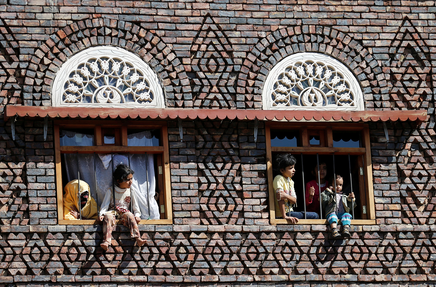 SANAA 2016-10-10 Children watch from the windows of their house as mourners pass during the funeral of Abdul Qader Helal, the mayor of Sanaa, the capital of Yemen, who was killed by an apparent Saudi-led air strike that ripped through a wake attended by some of the country's top political and security officials in Sanaa, October 10, 2016. REUTERS/Khaled Abdullah Photo: / REUTERS / TT / kod 72000