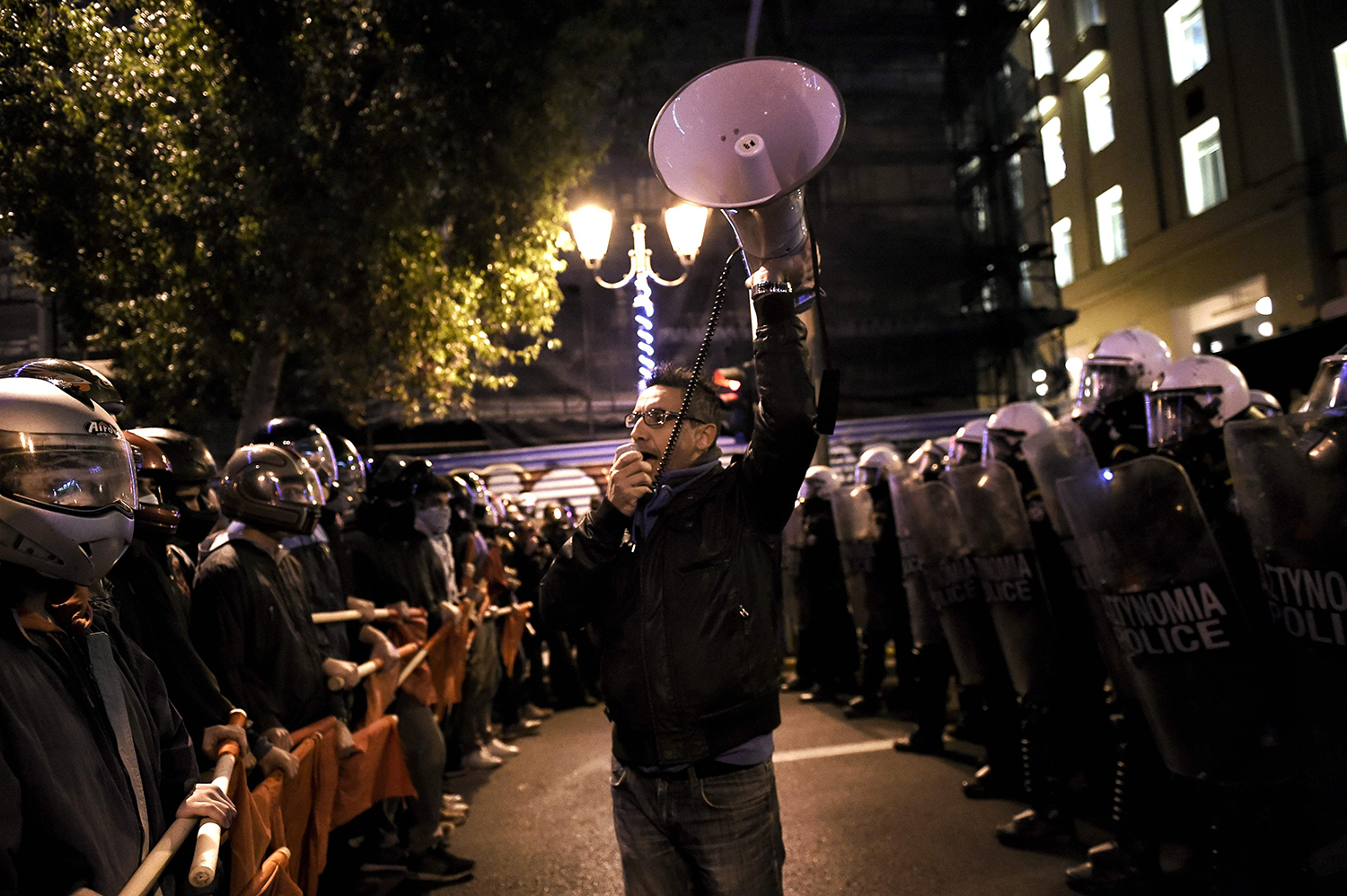 TOPSHOT - A man speaks into a megaphone as demonstrators hold red flags during a protest against the visit of the US president in Athens on November 15, 2016. US President Barack Obama is in Greece on a two-day official visit. / AFP PHOTO / ARIS MESSINIS / TT / kod 444