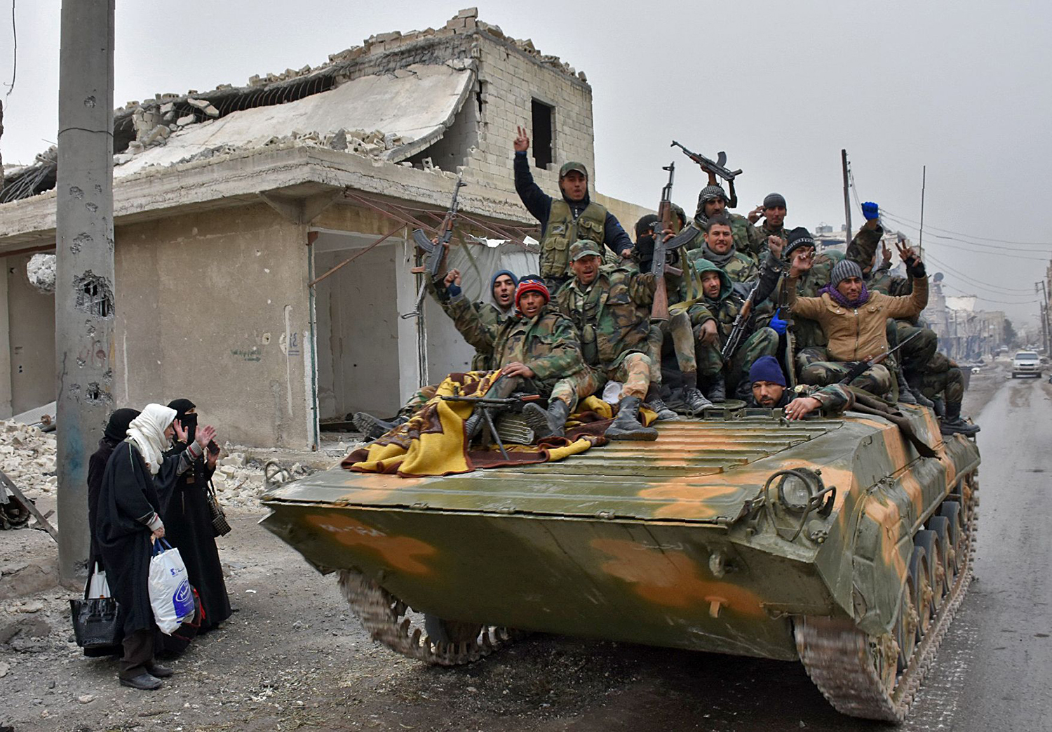 TOPSHOT - Syrian pro-government forces sit on a military vehicle driving past residents fleeing the eastern part of Aleppo and gathering in Masaken Hanano, a former rebel-held district which was retaken by the regime forces last week, on November 30, 2016. More than 50,000 Syrians have joined a growing exodus of terrified civilians from the besieged rebel-held east of Aleppo, the Syrian Observatory for Human Rights monitor said, as the UN Security Council was set for emergency talks on fighting in the city. Regime forces and allied fighters now fully control the city's northeast and pressed their offensive on November 30 on Aleppo's southeastern edges, advancing in the Sheikh Saeed district, according to state news agency SANA. / AFP PHOTO / George OURFALIAN / TT / kod 444