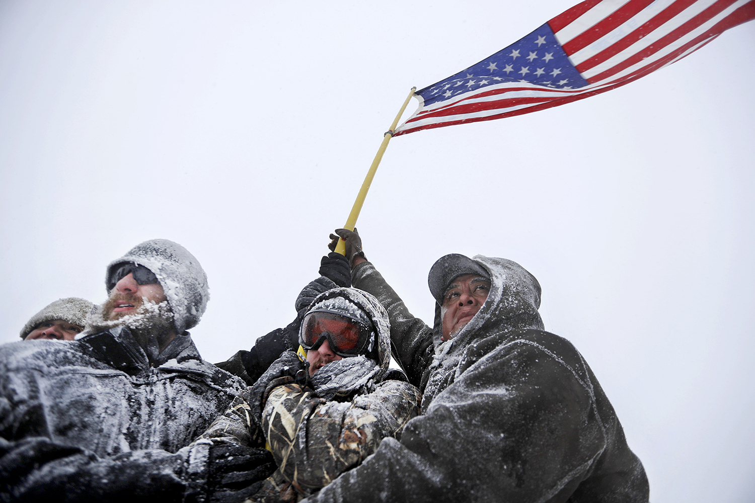 Military veterans huddle together to hold a United States flag against strong winds during a march to a closed bridge outside the Oceti Sakowin camp where people have gathered to protest the Dakota Access oil pipeline in Cannon Ball, N.D., Monday, Dec. 5, 2016. (AP Photo/David Goldman)