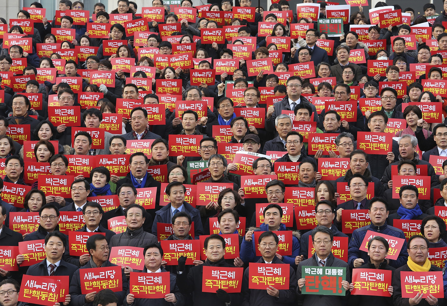 """FILE - In this Wednesday, Dec. 7, 2016, file photo, lawmakers and members of opposition parties hold cards during a rally demanding the impeachment of South Korean President Park Geun-hye at the National Assembly in Seoul, South Korea. South Korean lawmakers on Friday impeached Park, a stunning and swift fall for the country's first female leader amid protests that drew millions into the streets in united fury. The sign read """"President Park Geun-hye"""" and """"Impeachment !"""". (AP Photo/Ahn Young-joon)"""