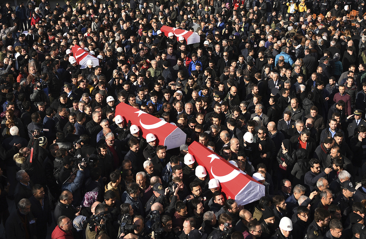People carry the coffins of bomb victims during a memorial in Istanbul, Sunday, Dec. 11, 2016, for police officers killed outside the Besiktas football club stadium Vodafone Arena late Saturday. Family members, Turkey's President Recep Tayyip Erdogan, ministers and colleagues attended the memorial as Turkey declared a national day of mourning Sunday after twin blasts in Istanbul killed dozens of people and wounded many others near a soccer stadium. Turkish authorities have banned distribution of images relating to the Istanbul explosions within Turkey. (AP Photo)