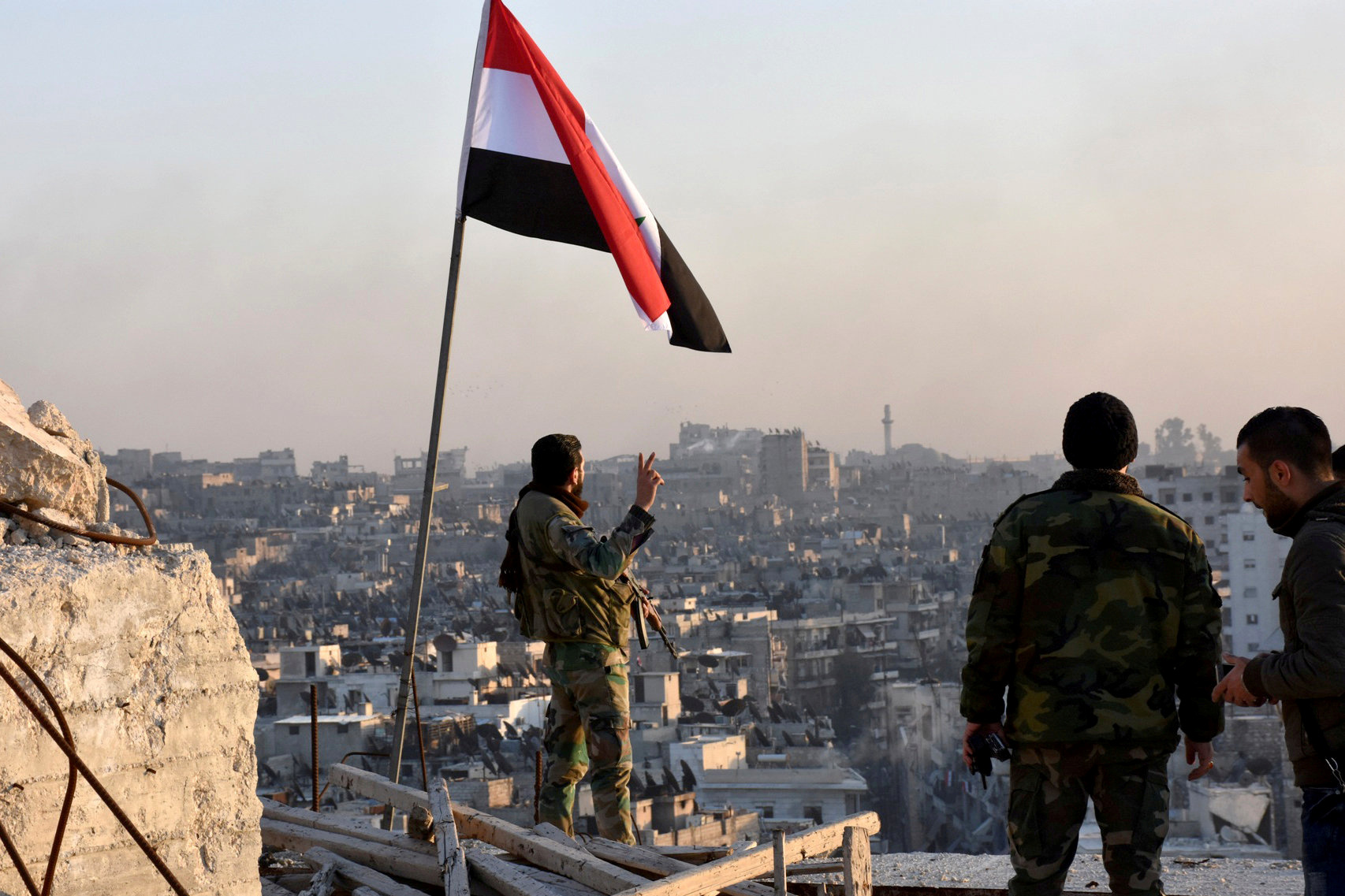 """ALEPPO 2016-12-14 A Syrian government soldier gestures a v-sign under the Syrian national flag near a general view of eastern Aleppo after they took control of al-Sakhour neigbourhood in Aleppo, Syria in this handout picture provided by SANA on November 28, 2016. SANA/Handout via REUTERS ATTENTION EDITORS - THIS IMAGE WAS PROVIDED BY A THIRD PARTY. EDITORIAL USE ONLY. REUTERS IS UNABLE TO INDEPENDENTLY VERIFY THIS IMAGE. SEARCH """"ALEPPO TIMELINE"""" FOR THIS STORY Photo: / REUTERS / TT / kod 72000"""