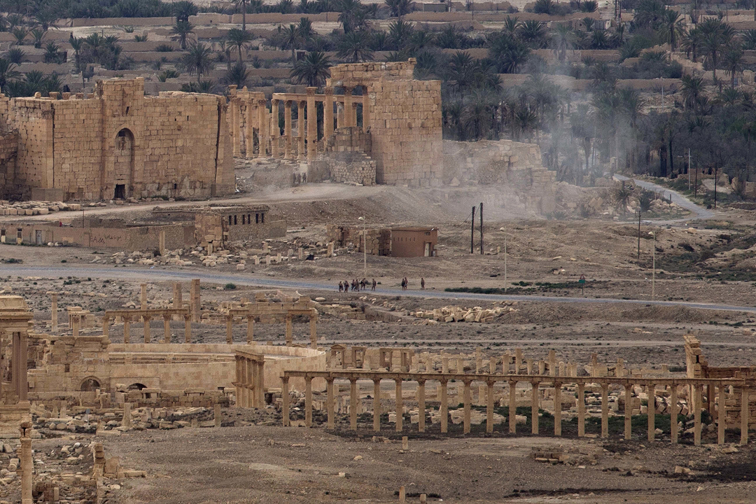 FILE -- In this April 14, 2016 file photo, Russian soldiers stand on a road as smoke rises from a controlled land mine detonation by Russian experts inside the ancient town of Palmyra, Syria in the central Homs province. Palmyra, the archaeological gem that Islamic State fighters retook Sunday, Dec. 11, 2016, from Syrian troops, is a desert oasis surrounded by palm trees, and a UNESCO world heritage site, that boasts 2,000-year-old towering Roman-era colonnades and priceless artifacts. It is also a strategic crossroads linking the Syrian capital, Damascus, with the country's east and neighboring Iraq. (AP Photo/Hassan Ammar, File)