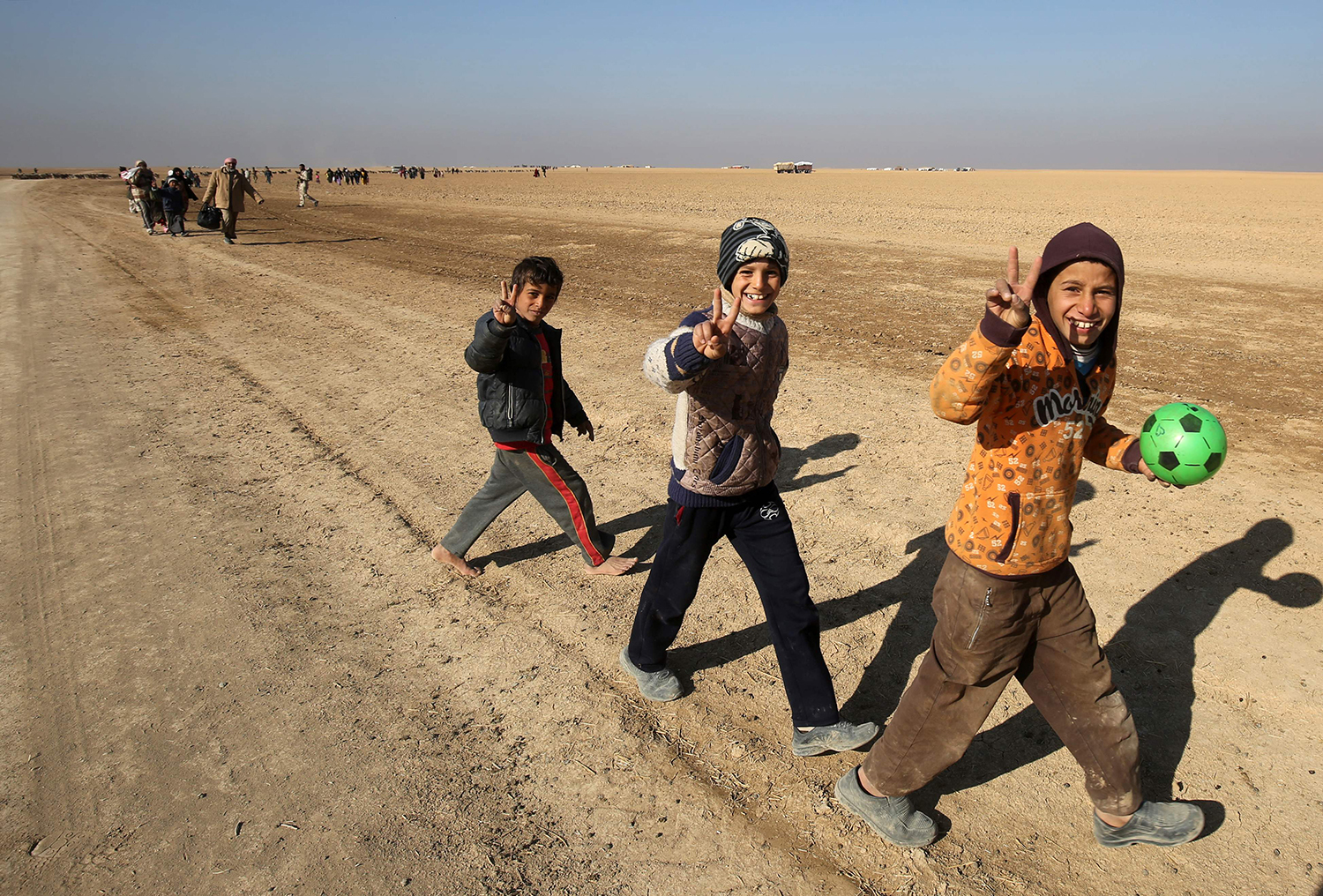 TOPSHOT - Iraqi boys, who fled their homes in the Iraqi town Shwah west of Mosul due to the fighting between government forces' and Islamic State (IS) group's jihadists, gesture as they are being escorted, from their makeshift camp to safer areas by Shiite fighters from the Hashed al-Shaabi (Popular Mobilisation) paramilitary forces, on December 11, 2016. According to the United Nations, about 90,000 people have fled their homes since the start of their offensive to retake the city of Mosul. / AFP PHOTO / AHMAD AL-RUBAYE / TT / kod 444
