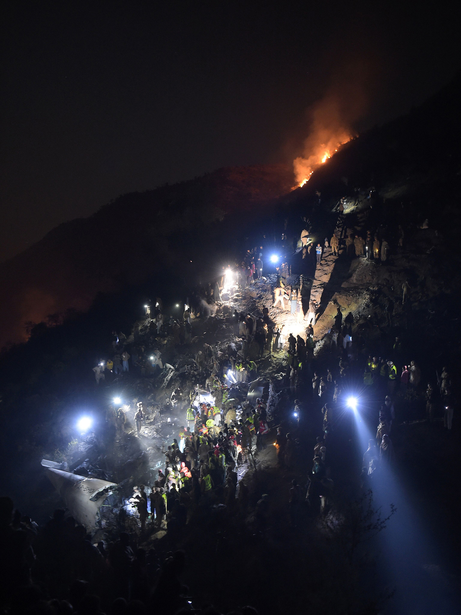 TOPSHOT - Pakistani soldiers and volunteers search for victims from the wreckage of the crashed PIA passenger plane Flight PK661 at the site in the village of Saddha Batolni in the Abbottabad district of Khyber Pakhtunkhwa province on December 7, 2016. A Pakistani plane carrying 48 people crashed on December 7, in the country's mountainous north and burst into flames killing everyone on board, authorities said, in one of the deadliest aviation accidents in the country's history. Pakistan International Airlines Flight PK661 came down while travelling from the city of Chitral to Islamabad, the civil aviation authority said. / AFP PHOTO / AAMIR QURESHI / TT / kod 444
