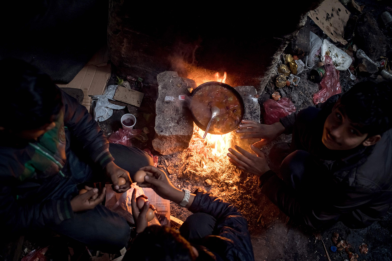 TOPSHOT - Migrants prepare a meal at a makeshift shelter at an abandoned warehouse in Belgrade on December 8, 2016. According to the latest figures, 6,300 migrants are stranded in Serbia. Hundreds of thousands of migrants had passed through Serbia in 2015 and early 2016. This road trough the Balkans had been closed in March after the borders of several countries, including Croatia, had been closed for migrants. / AFP PHOTO / ANDREJ ISAKOVIC / TT / kod 444