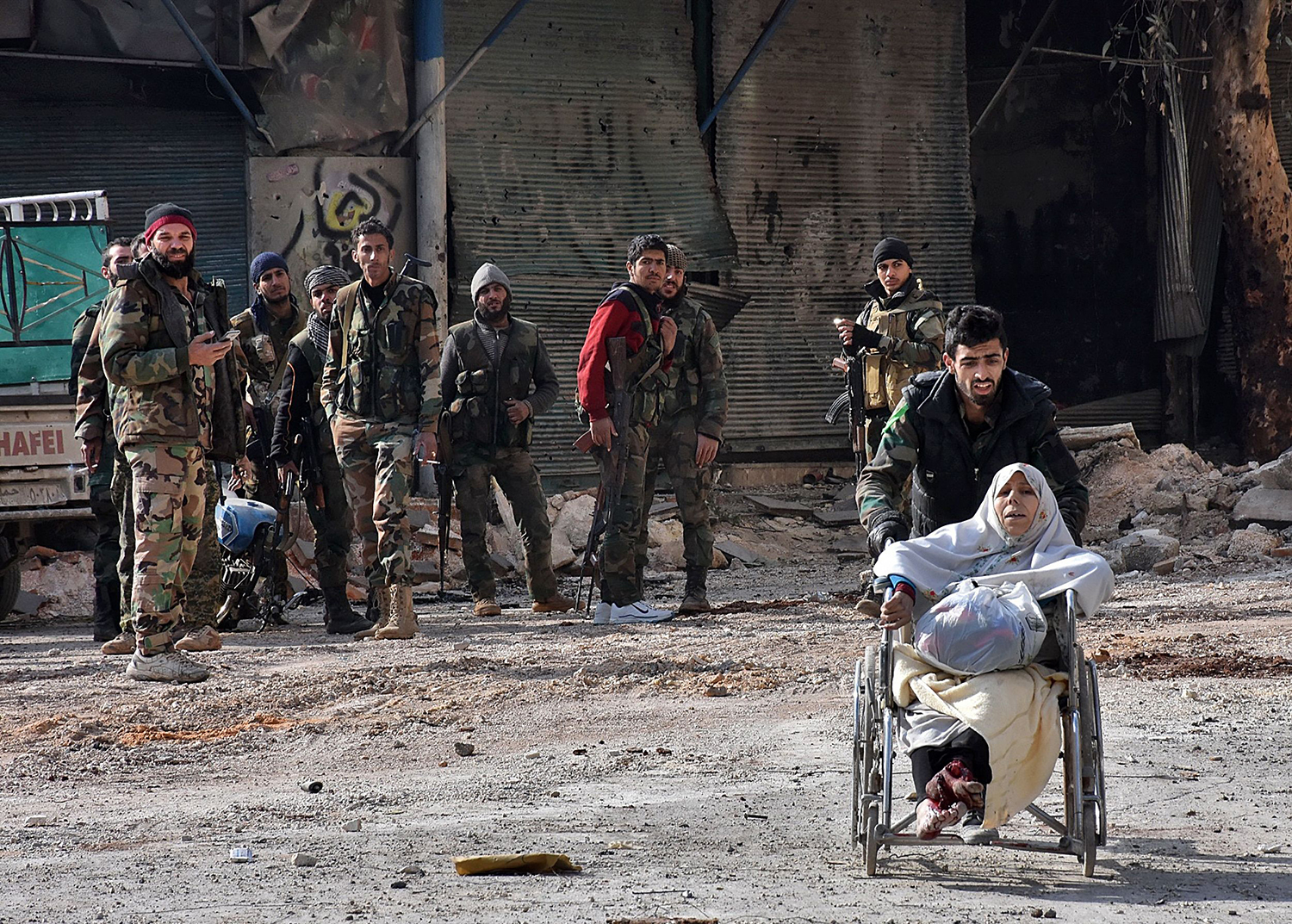 TOPSHOT - A member of the government forces pushes an injured woman in a wheelchair as civilians are evacuated from Aleppo's al-Shaar neighbourhood after government forces took control of the area in the eastern part of the northern Syrian city on December 7, 2016. Rebels in Aleppo called for a five-day truce and the evacuation of civilians after losing more than three quarters of their territory including the Old City to a Syrian army offensive. / AFP PHOTO / GEORGE OURFALIAN / TT / kod 444