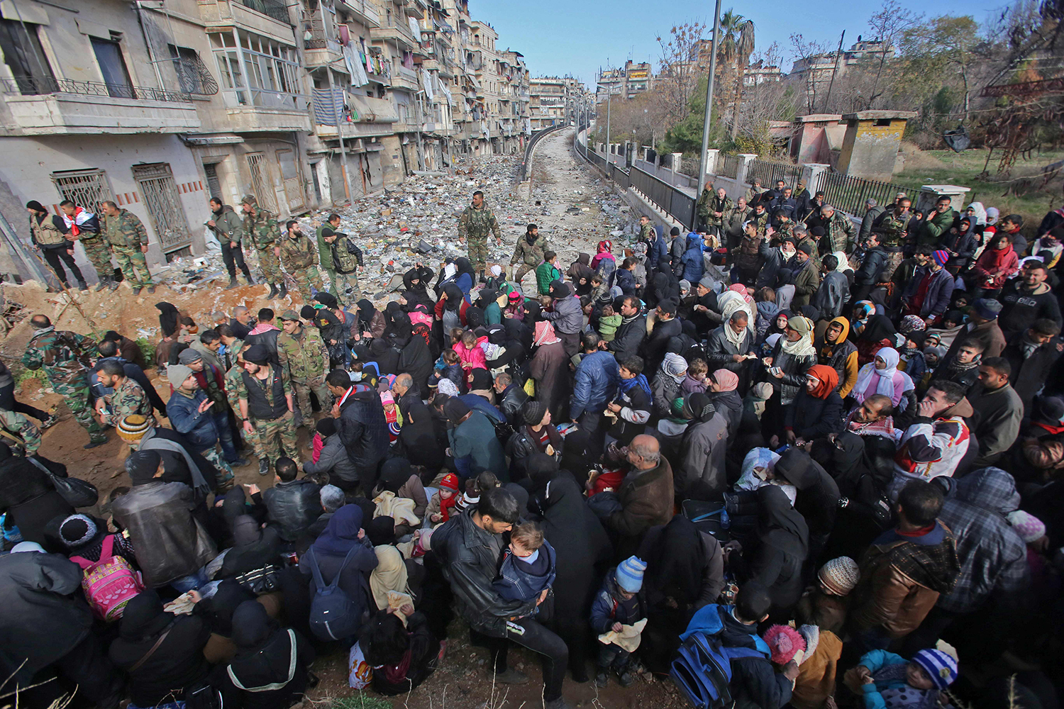 TOPSHOT - Syrian residents fleeing the violence gather at a checkpoint, manned by pro-government forces, in the Maysaloun neighbourhood of the northern embattled Syrian city of Aleppo on December 8, 2016. Syria's army battled to take more ground from rebels in Aleppo after President Bashar al-Assad said victory for his troops in the city would be a turning point in the war. / AFP PHOTO / Youssef KARWASHAN / TT / kod 444