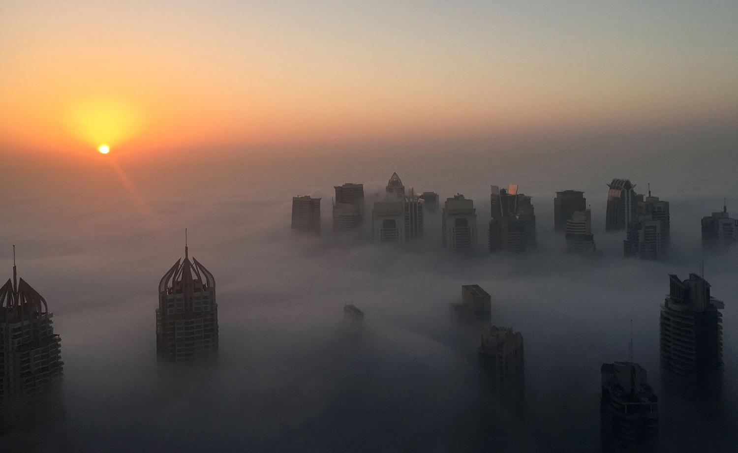 TOPSHOT - The sun rises behind skyscrapers amidst the clouds on a foggy morning in Dubai on December 5, 2016. / AFP PHOTO / RENE SLAMA / TT / kod 444