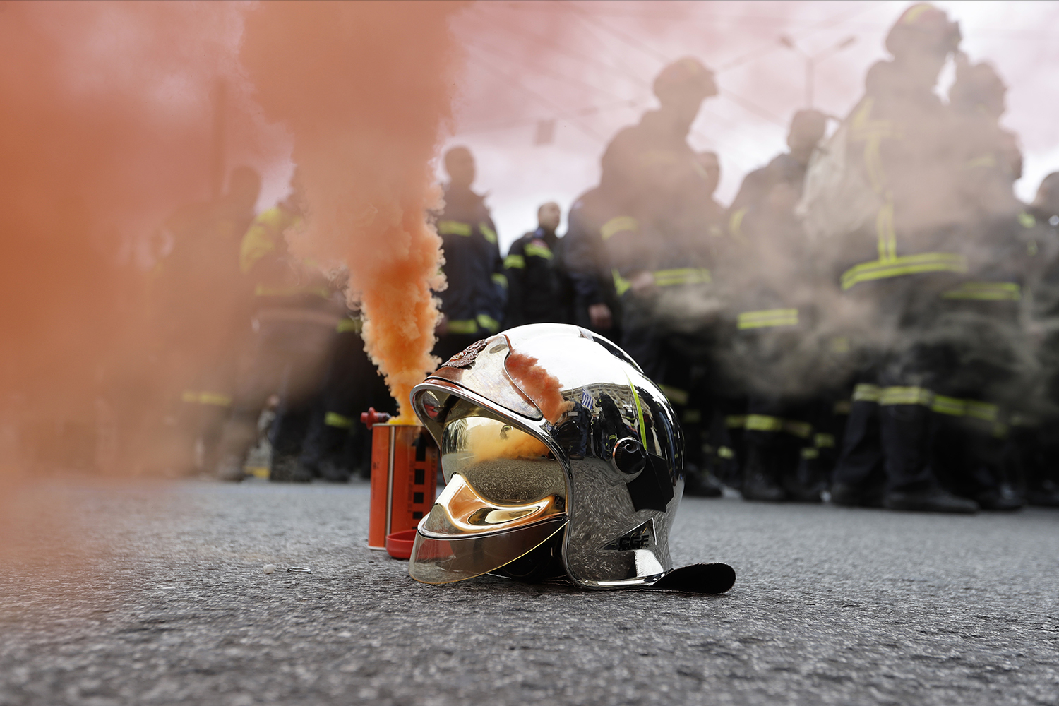 A firefighter's helmet stands next to a flare during a protest in central Athens, on Wednesday, Feb. 8 2017. Hundreds of firefighters in uniform have taken to the streets of the Greek capital to protest hiring conditions. (AP Photo/Thanassis Stavrakis)