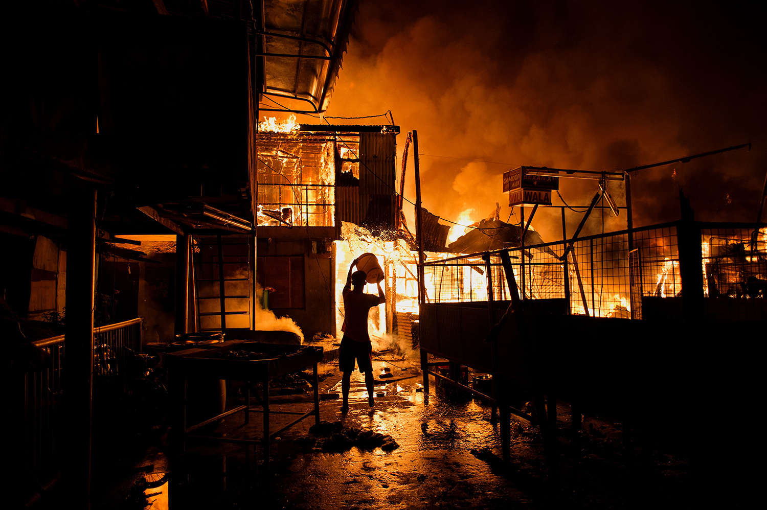 """TOPSHOT - CORRECTION - A resident pours water on a fire as it destroys hundreds of houses at an informal settlers community in Delpan, Tondo, Manila on February 7, 2017. / AFP PHOTO / NOEL CELIS / """"The erroneous mention[s] appearing in the metadata of this photo by NOEL CELIS has been modified in AFP systems in the following manner: [February] instead of [January]. Please immediately remove the erroneous mention[s] from all your online services and delete it (them) from your servers. If you have been authorized by AFP to distribute it (them) to third parties, please ensure that the same actions are carried out by them. Failure to promptly comply with these instructions will entail liability on your part for any continued or post notification usage. Therefore we thank you very much for all your attention and prompt action. We are sorry for the inconvenience this notification may cause and remain at your disposal for any further information you may require."""" / TT / kod 444"""