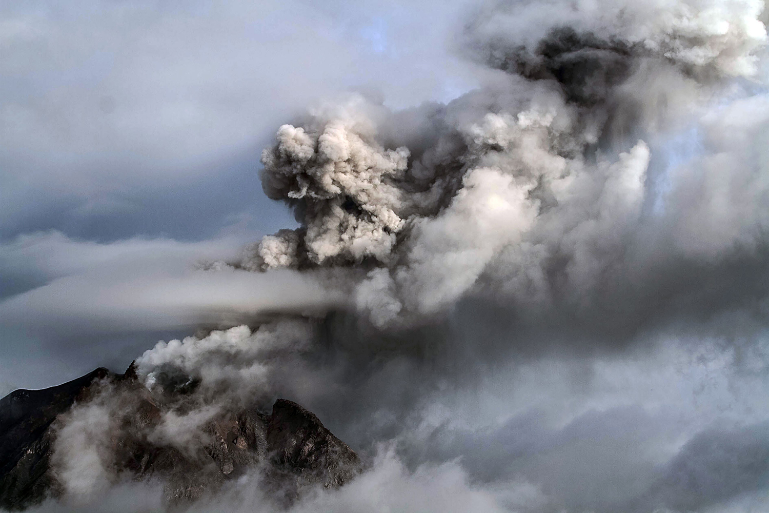 TOPSHOT - Mount Sinabung volcano spews thick volcanic ash as seen from Beganding village in Karo on February 7, 2017. Many residents in the area have been forced to relocate to other villages of Northern Sumatra at a safer distance from mount Sinabung volcano, one of the most active in Indonesia. / AFP PHOTO / STR / TT / kod 444