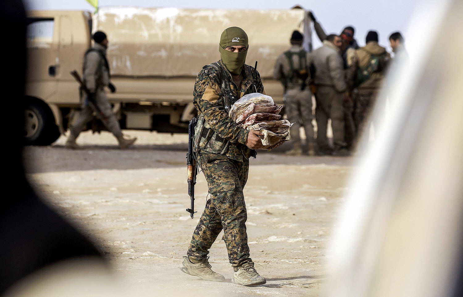 """TOPSHOT - A member of the Syrian Democratic Forces (SDF), made up of US-backed Kurdish and Arab fighters, carries supplies near the village of Bir Fawaz, 20 km north of Raqa, during their offensive towards the Islamic State (IS) group's Syrian stronghold as part of the third phase to retake the city and its surroundings, on February 8, 2017. The Islamic State group is """"completely besieged"""" in its last major stronghold in Syria's Aleppo province, a monitor said, as pro-regime forces pressure the jihadists on several fronts. / AFP PHOTO / DELIL SOULEIMAN / TT / kod 444"""