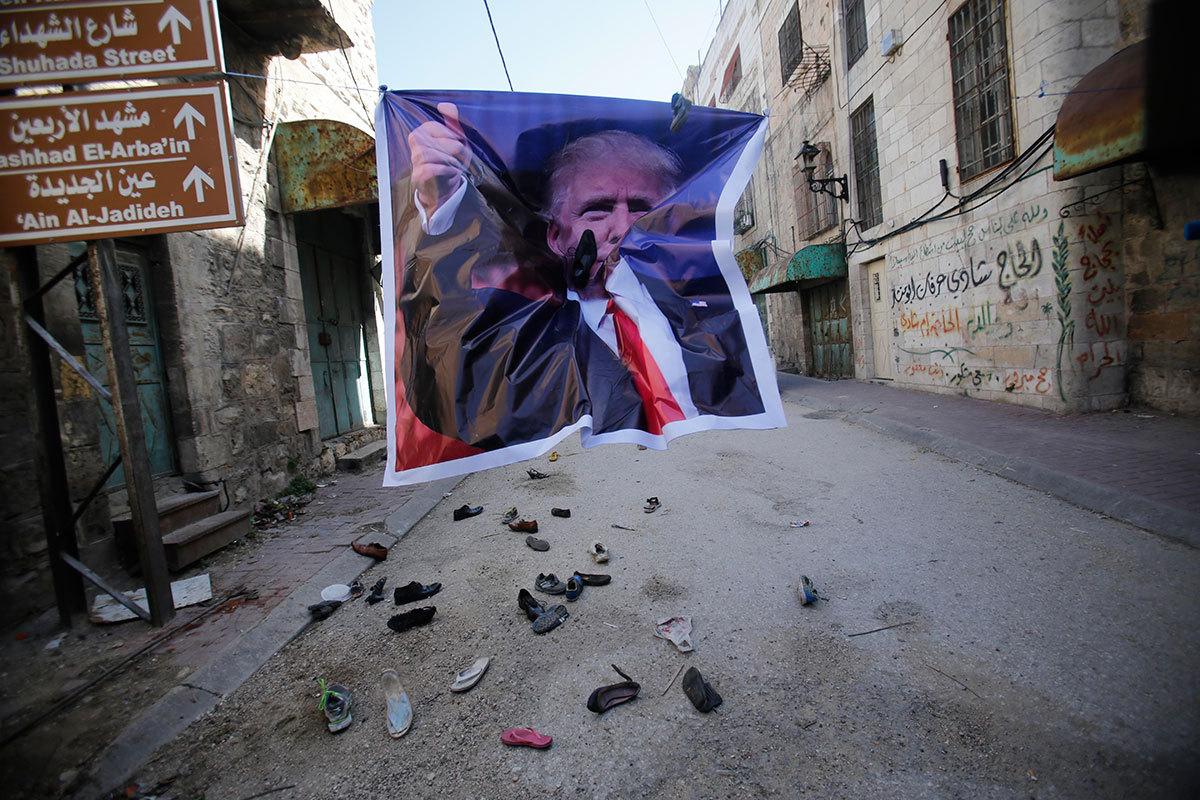 Demonstranter i Hebron, på Västbanken, kastar skor på en poster med Donald Trumps porträtt. NASSER SHIYOUKHI / AP