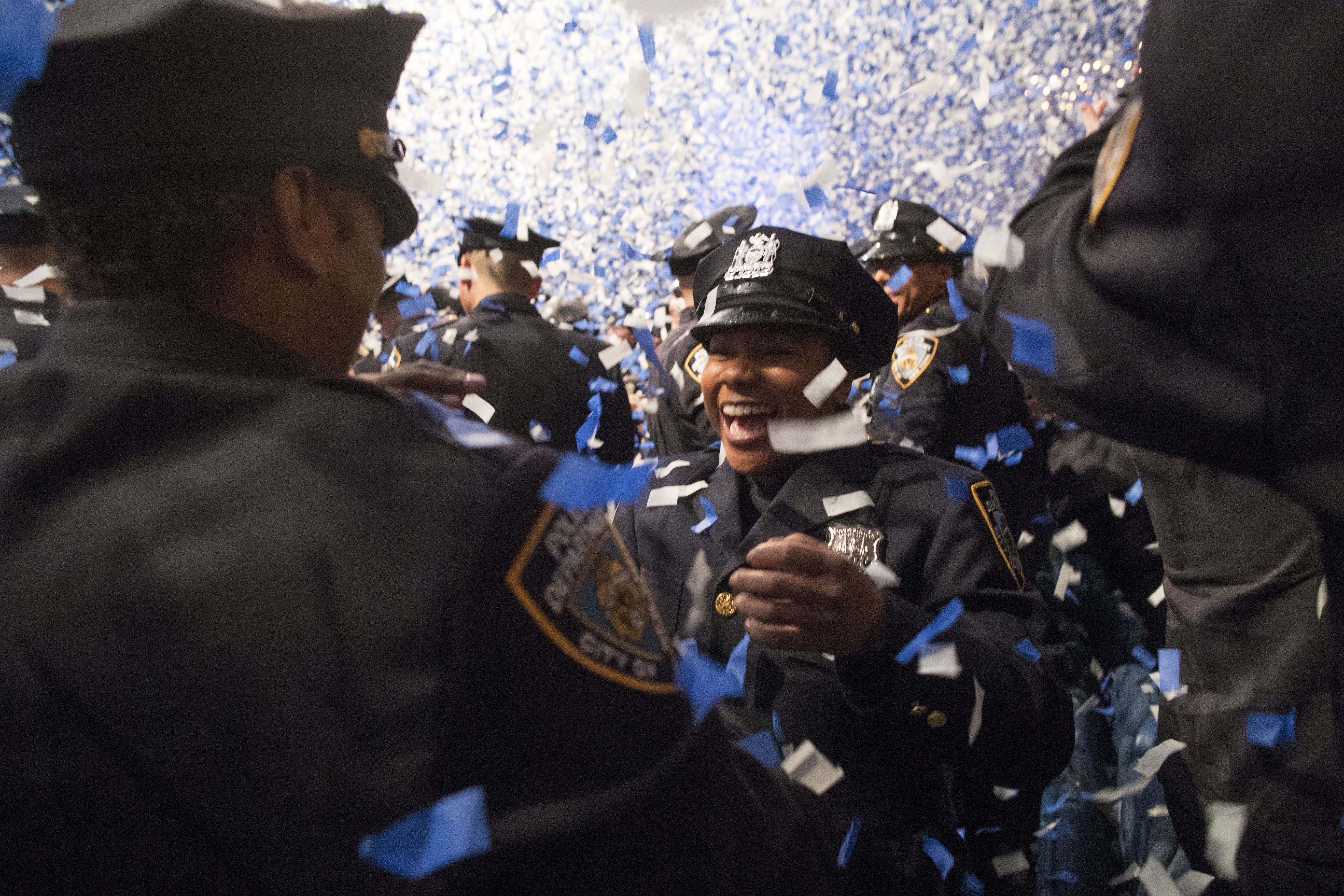 The newest members of the New York City police officers hug during their graduation ceremony, Thursday, March 30, 2017, in New York. Over 600 men and women took the oath of office and pledged to protect the people of New York City. (AP Photo/Mary Altaffer)