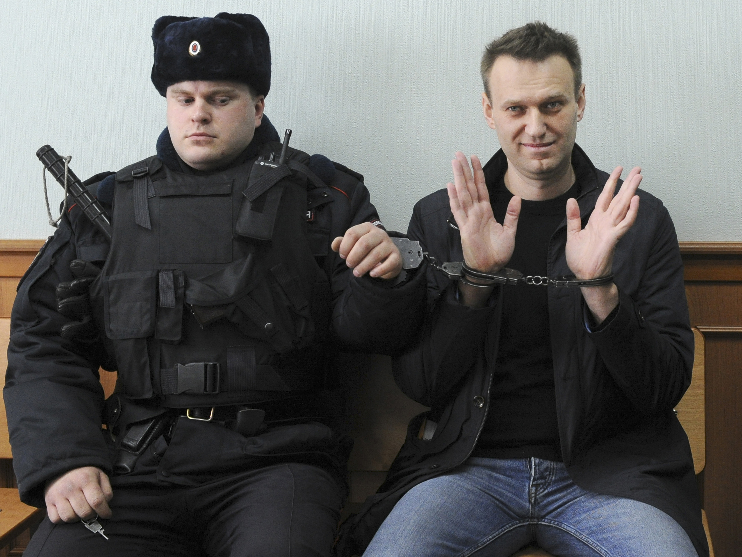 Russian opposition leader Alexei Navalny, right, poses for press in court in Moscow, Russia, Thursday, March 30, 2017. Navalny attends a court hearing on his appeal. Navalny, who organized a wave of nationwide protests against government corruption was sentenced to 15 days in jail.(AP Photo)