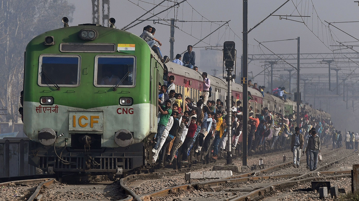 TOPSHOT - Indian passengers hang onto a train as it departs from a station on the outskirts of New Delhi on February 28, 2017. India's economic growth rate fell to seven percent in the third quarter of the financial year after the controversial ban on high-value banks notes in November, the government said. Gross domestic product in one of the world's fastest growing economies expanded 7.0 percent year-on-year in the three months to the end of December, down from 7.3 percent in the previous quarter, official figures showed. / AFP PHOTO / Prakash SINGH / TT / kod 444