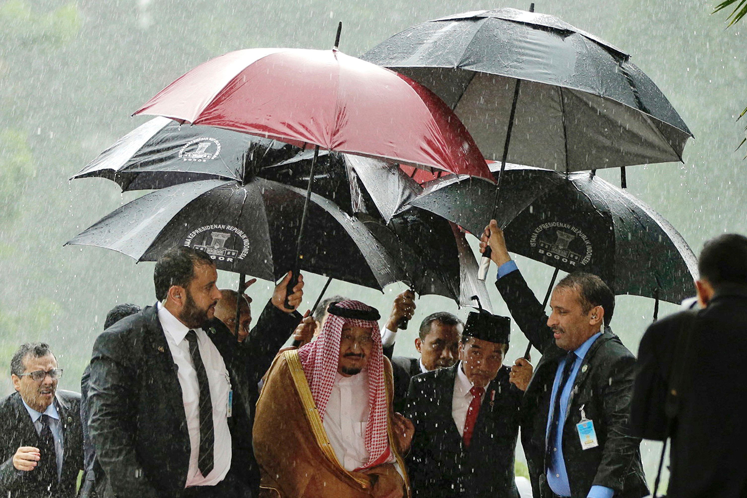 TOPSHOT - Saudi Arabia's King Salman bin Abdul Aziz (centre L) and Indonesia's President Joko Widodo (centre R) walk in heavy rain at the presidential palace in Bogor, West Java on March 1, 2017. Cheering crowds welcomed King Salman on March 1 as he began the first visit by a Saudi monarch to Indonesia for almost 50 years, seeking stronger economic ties with the world's most populous Muslim-majority country. / AFP PHOTO / POOL / Achmad Ibrahim / TT / kod 444
