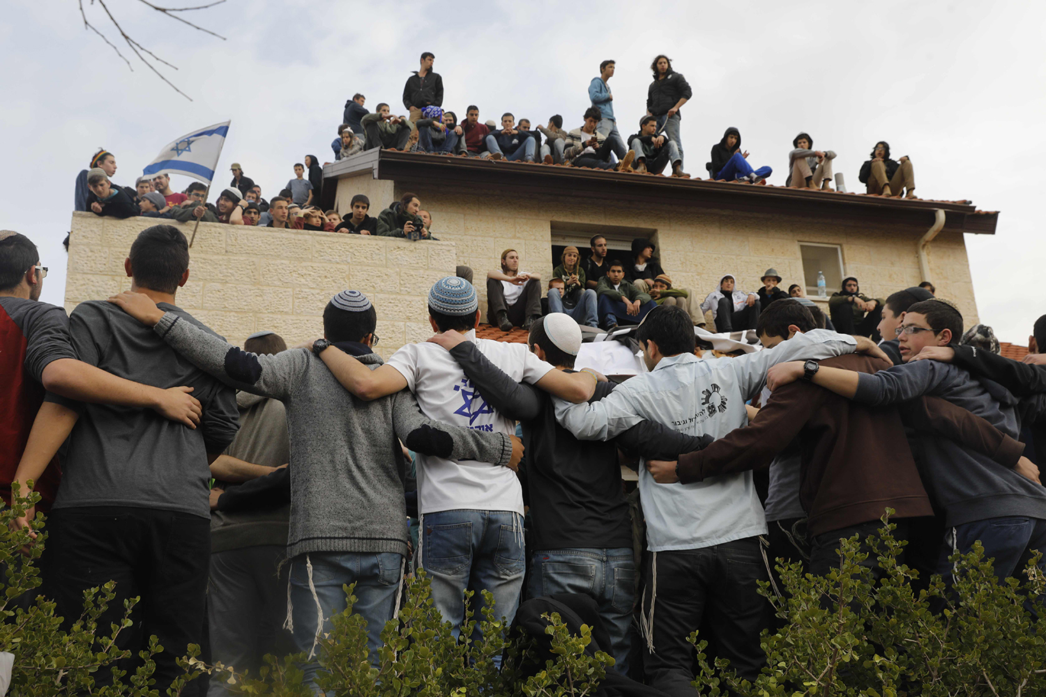 TOPSHOT - Israeli youths supporters of settlements surround and sit on a rooftop of a house which is due to be emptied and demolished in the settlement of Ofra in the occupied West Bank, during an operation by Israeli forces to evict the houses, on February 28, 2017. Nine homes in the Ofra settlement were found to have been built on private Palestinian land and the Israeli supreme court ordered them razed by March 5, rejecting last minute petitions to delay the demolition or have the buildings sealed instead. / AFP PHOTO / MENAHEM KAHANA / TT / kod 444