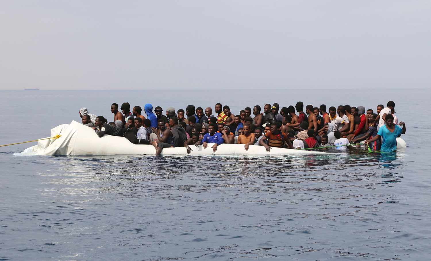 TOPSHOT - Migrants wait to be rescued from a sinking dingey off the Libyan coasal town of Zawiyah, east of the capital, on March 20, 2017, as they attempted to cross from the Mediterranean to Europe. Libya has long been a stepping stone for migrants dreaming of a better life in Europe, but people smugglers have stepped up their lucrative trade in the chaos since the 2011 ouster of longtime dictator Moamer Kadhafi. / AFP PHOTO / Abdullah ELGAMOUDI / TT / kod 444