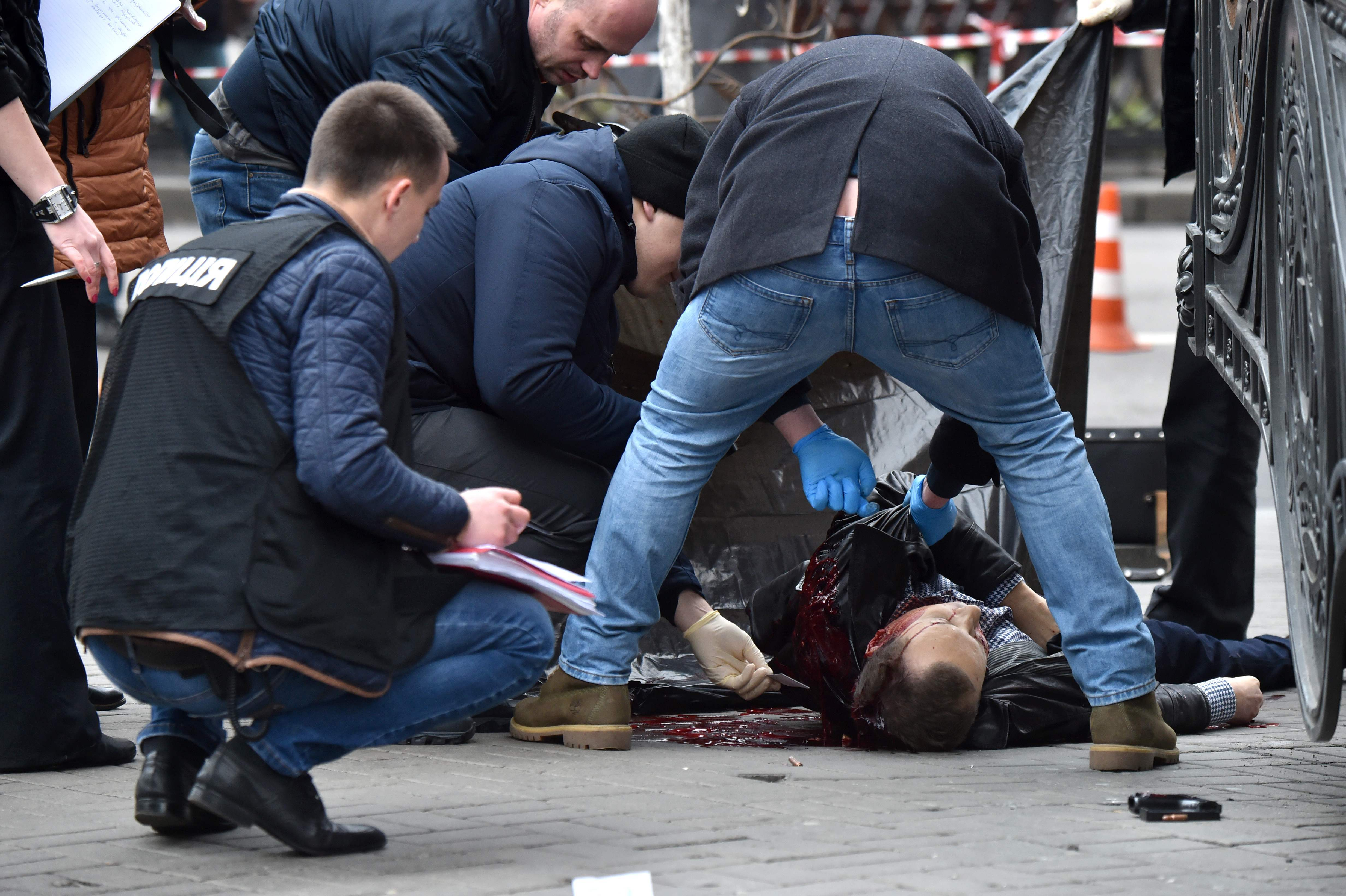 """TOPSHOT - EDITORS NOTE: Graphic content / Ukrainian police experts examine the body of former Russian MP Denis Voronenkov after he was shot dead on March 23, 2017 in the center of Kiev. Ukrainian President blamed Russia for the murder of Voronenkov, who moved to Ukraine last year and was wanted by Russia for fraud, saying it was an """"act of state terrorism."""" / AFP PHOTO / Sergei SUPINSKY / TT / kod 444"""