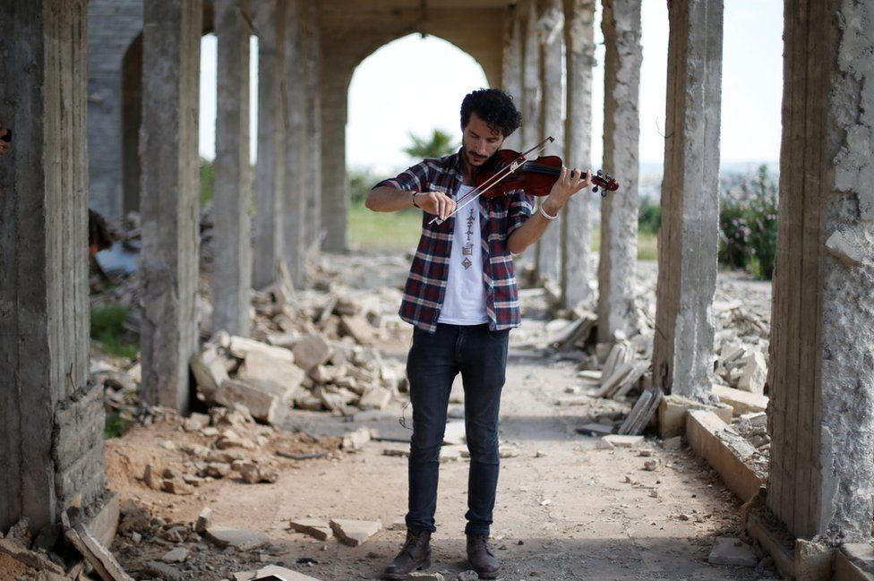 Ameen Mukdad, a violinist who lived under so-called Islamic State for two-and-a-half years, performs at Nabi Yunus, a shrine in eastern Mosul, Iraq, following liberation. MUHAMMAD HAMED / REUTERS