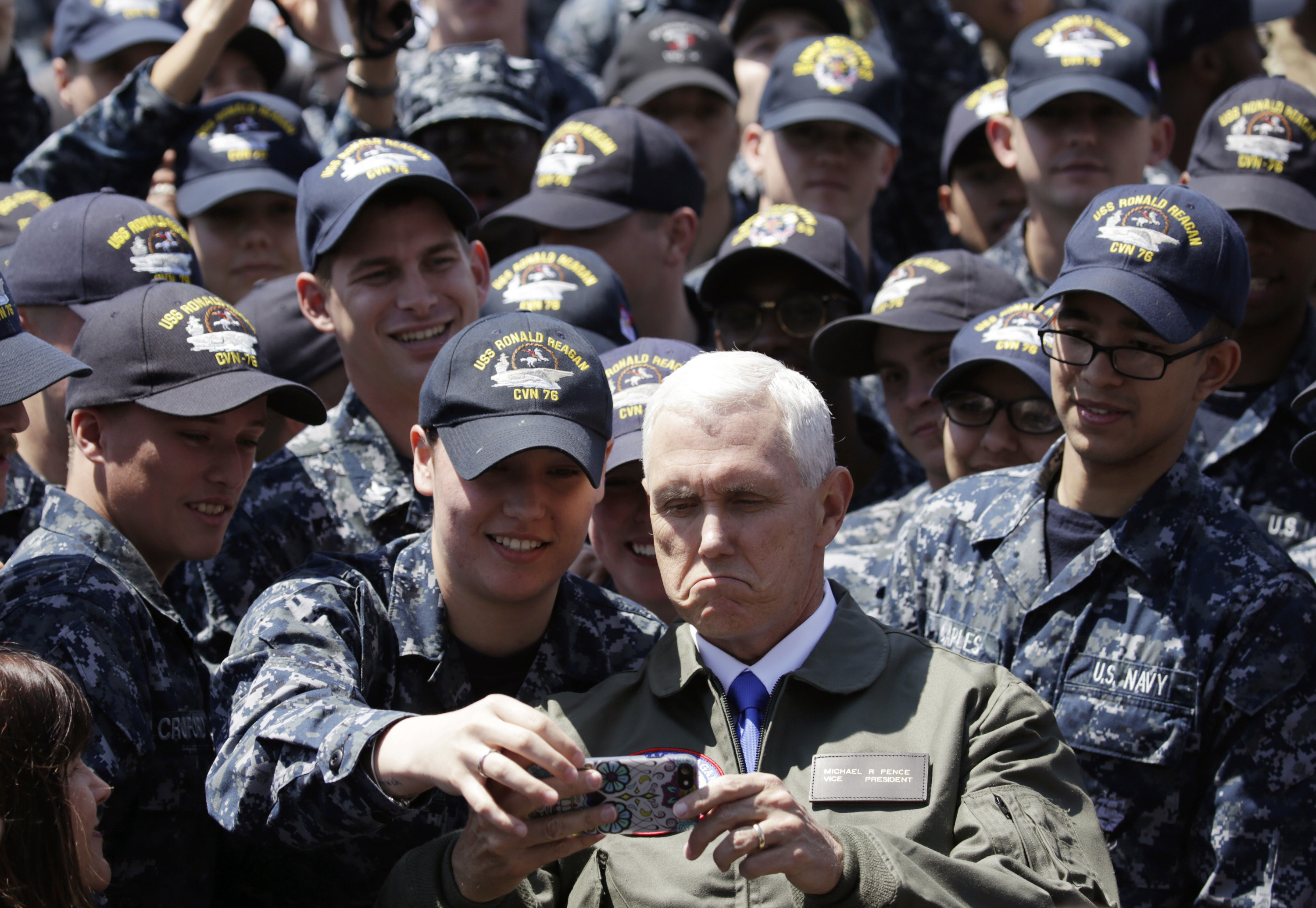 U.S. Vice President Mike Pence, center right at bottom, takes a selfie with U.S. servicemen on the flight deck of U.S. navy nuclear-powered aircraft carrier USS Ronald Reagan, at the U.S. Navy's Yokosuka base in Yokosuka, south of Tokyo, Wednesday, April 19, 2017. (AP Photo/Eugene Hoshiko)