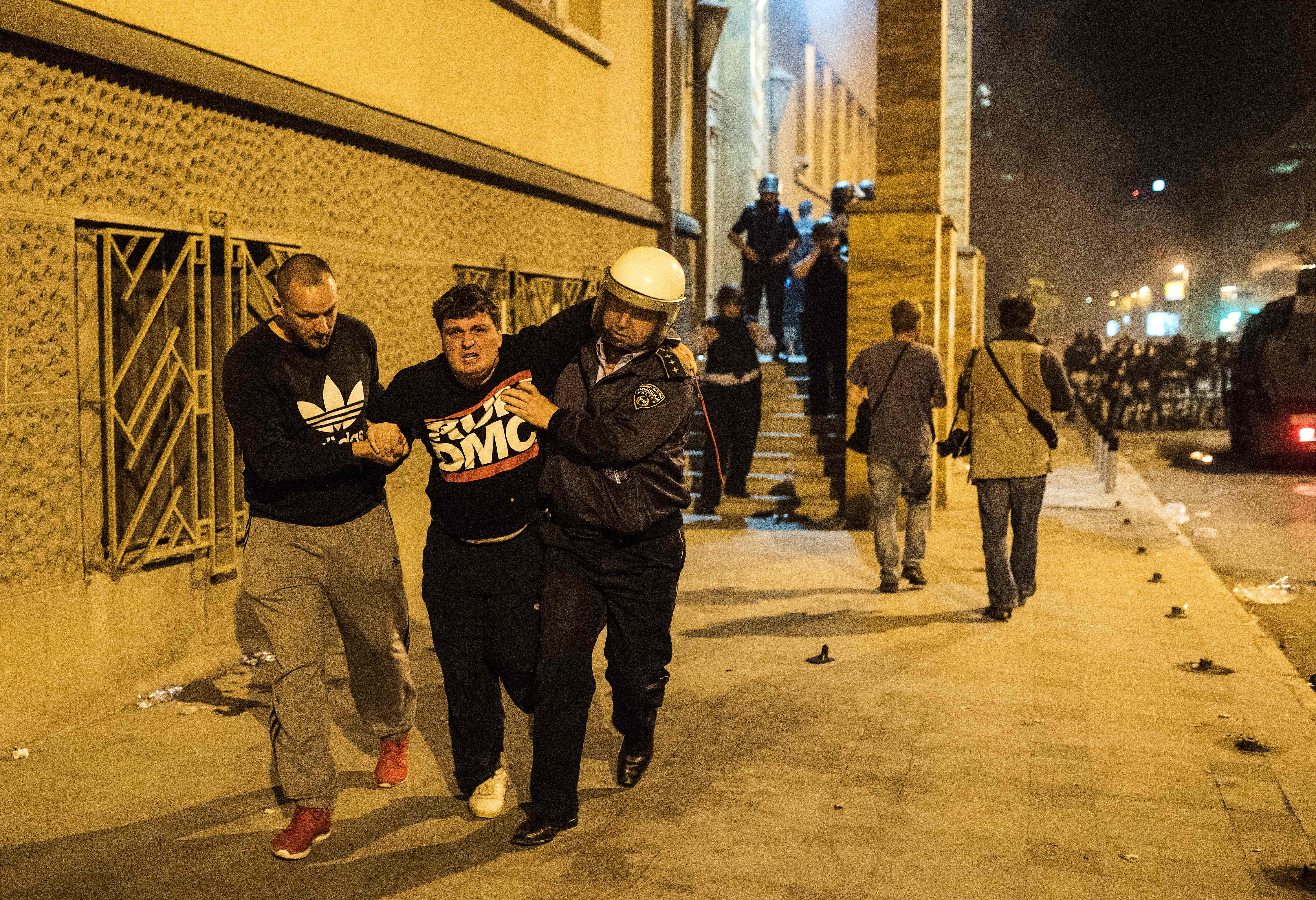 Policemen carry an injured man as protesters clash with police after the governing Social Democrats and ethnic Albanian parties voted to elect an Albanian as parliament speaker in Skopje on April 27, 2017. Macedonia's opposition leader was among at least 10 people injured in parliament on April 27 after protesters stormed the building following an allegedly unfair vote for a parliamentary speaker, witnesses and local media reported. The violence erupted after around 100 protesters supporting the rival VMRO-DPMNE party entered parliament waving Macedonian flags and singing the national anthem. / AFP PHOTO / Robert ATANASOVSKI / TT / kod 444