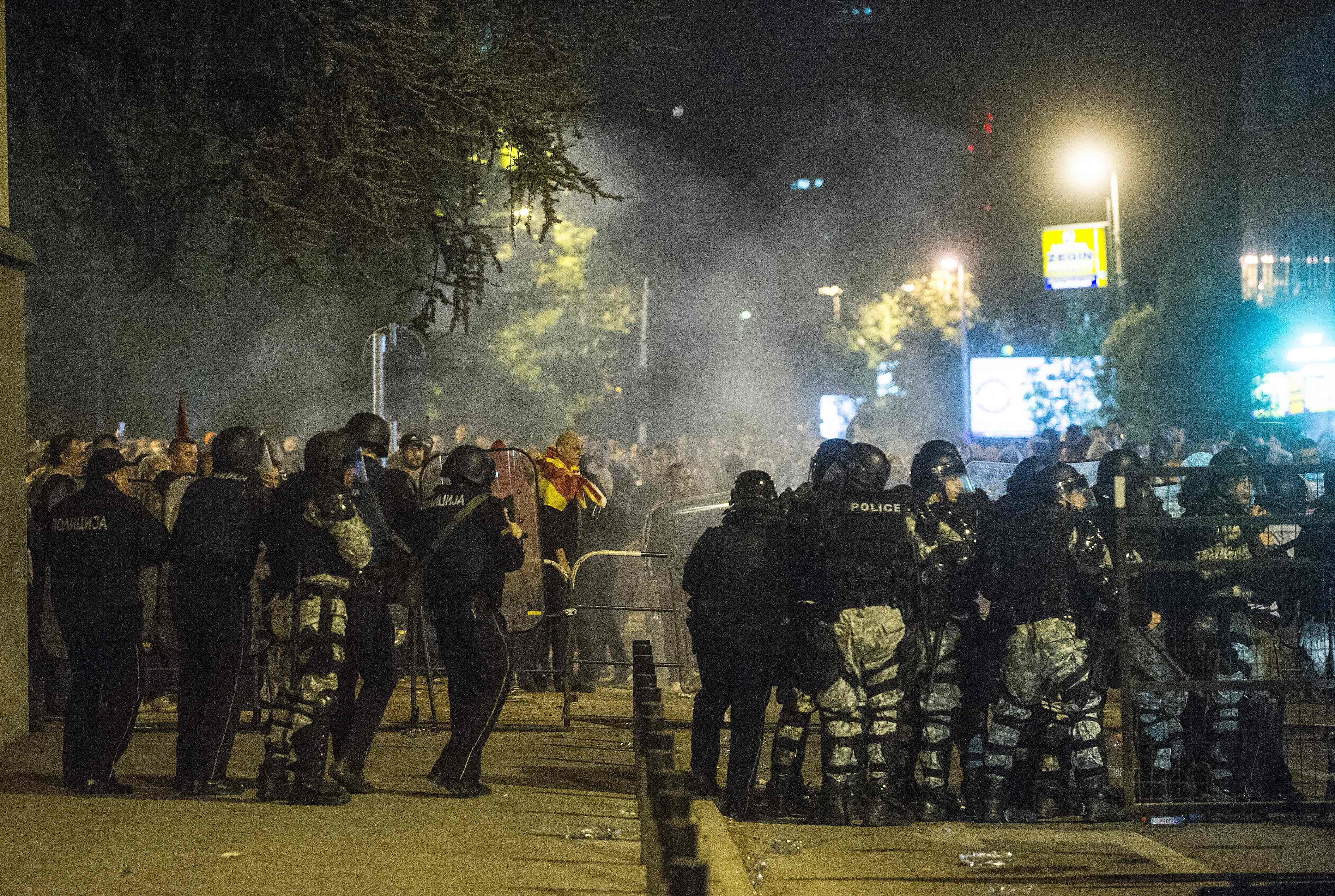 Police face protesters gathered outside Macedonia's parliament after the governing Social Democrats and ethnic Albanian parties voted to elect an Albanian as parliament speaker in Skopje on April 27, 2017. Macedonia's opposition leader was among at least 10 people injured in parliament on April 27 after protesters stormed the building following an allegedly unfair vote for a parliamentary speaker, witnesses and local media reported. The violence erupted after around 100 protesters supporting the rival VMRO-DPMNE party entered parliament waving Macedonian flags and singing the national anthem. / AFP PHOTO / Robert ATANASOVSKI / TT / kod 444