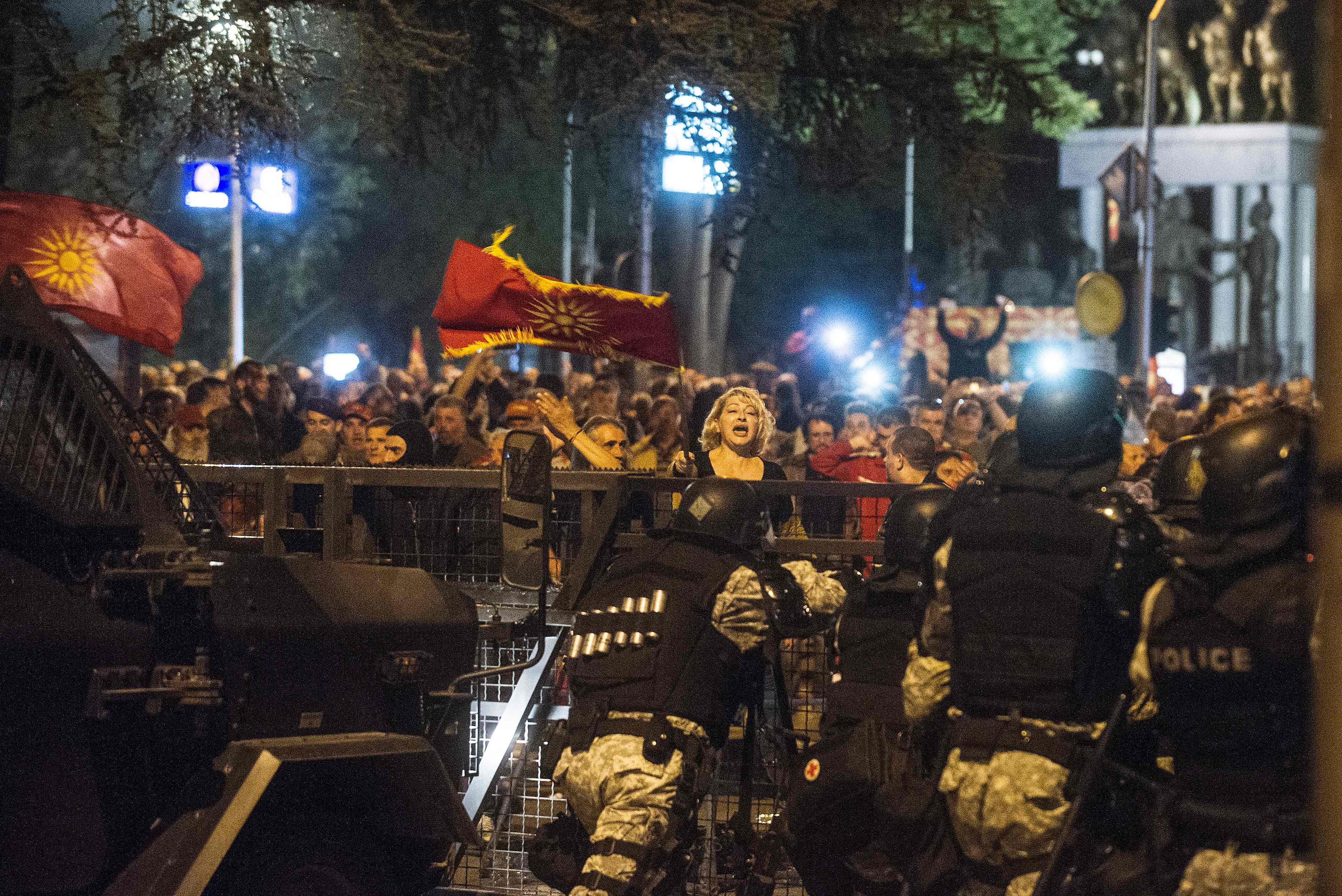 A woman waves a flag in front of police blocking the entrance to Macedonia's parliament as protesters gather after the governing Social Democrats and ethnic Albanian parties voted to elect an Albanian as parliament speaker in Skopje on April 27, 2017. Macedonia's opposition leader was among at least 10 people injured in parliament on April 27 after protesters stormed the building following an allegedly unfair vote for a parliamentary speaker, witnesses and local media reported. The violence erupted after around 100 protesters supporting the rival VMRO-DPMNE party entered parliament waving Macedonian flags and singing the national anthem. / AFP PHOTO / Robert ATANASOVSKI / TT / kod 444