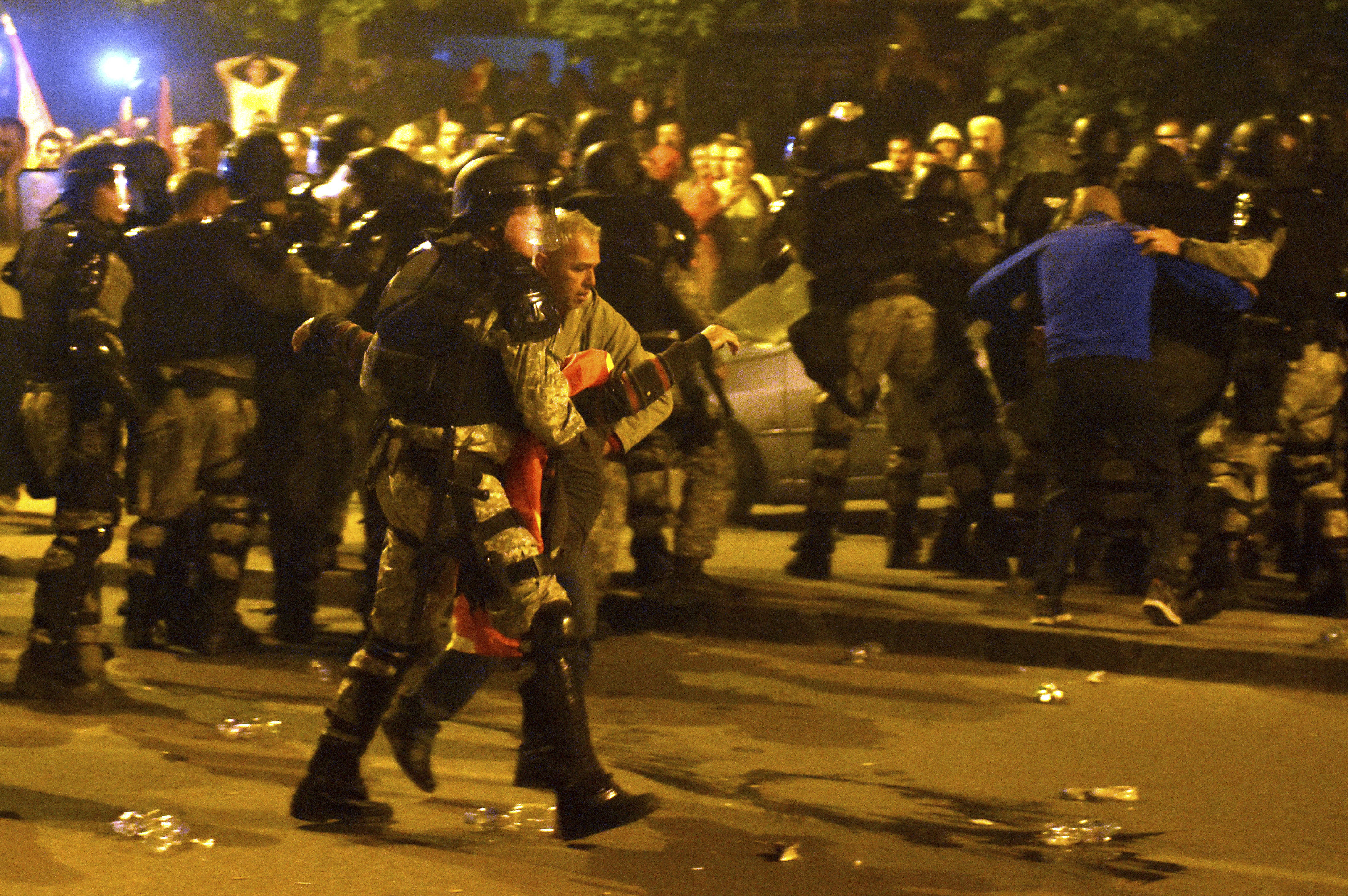 A police officer helps an injured protester during clashes in front of the parliament building in Skopje, Macedonia, Thursday, April 27, 2017. Chaos swept into Macedonia's parliament Thursday as demonstrators stormed the building and attacked lawmakers to protest the election of a new speaker despite a months-old deadlock in efforts to form a new government. (AP Photo/Dragan Perkovski)